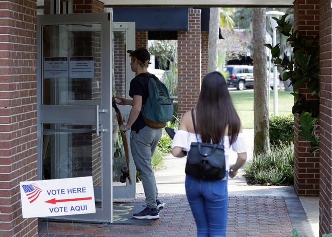 In this Wednesday, Oct. 31, 2018 photo, students enter a polling place to cast their ballots during a Vote for Our Lives event at the University of Central Florida in Orlando, Fla.