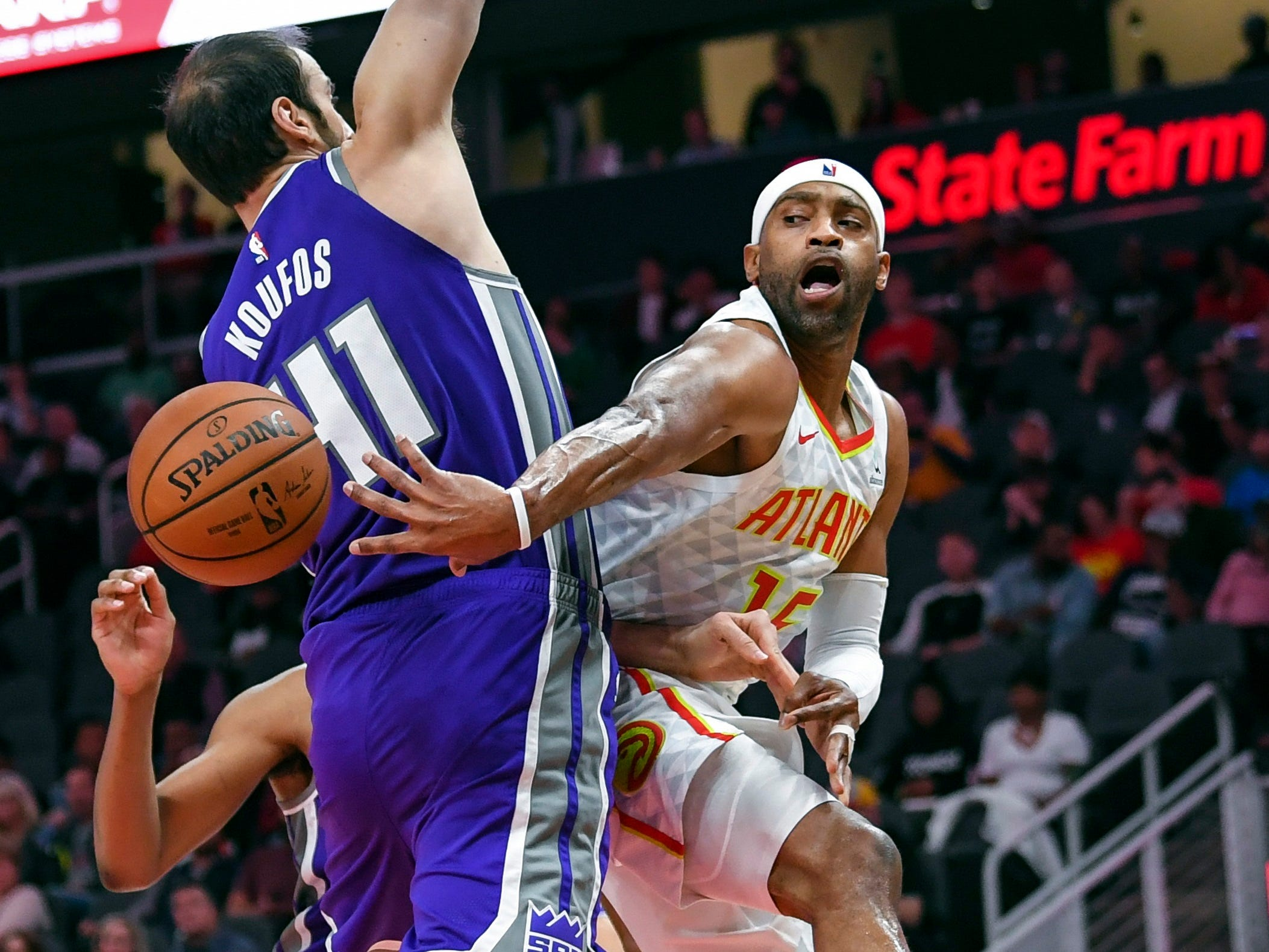 Nov. 1: Hawks guard and oldest player in the league Vince Carter (15) shows he's still got it with a slick pass around Kings defender Kosta Koufos (41) during the second half in Atlanta.
