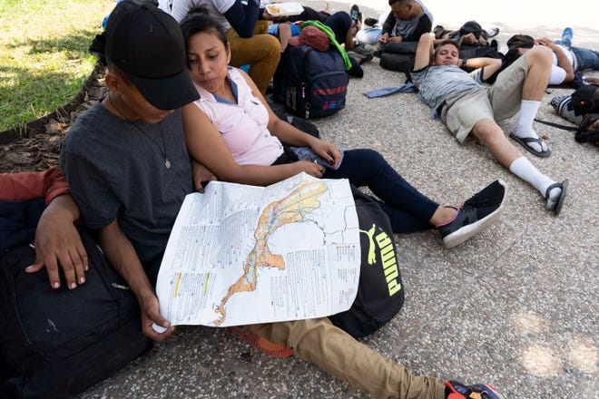 Kevin Vladimir, from El Salvador, looks at the route map while he joined another mass exodus of migrants, this time from El Salvador, was preparing to cross into Mexico from Guatemala Thursday, the large wave in less than two weeks. While Mexican immigration officers have started allowing small groups of 50 to 200 migrants to cross the international bridge between Tecun Uman, Guatemala and Ciudad Hidalgo, to give them the chance to apply to remain in Mexico as refugees, some migrants feared the offer was a trap to arrest and deport them.