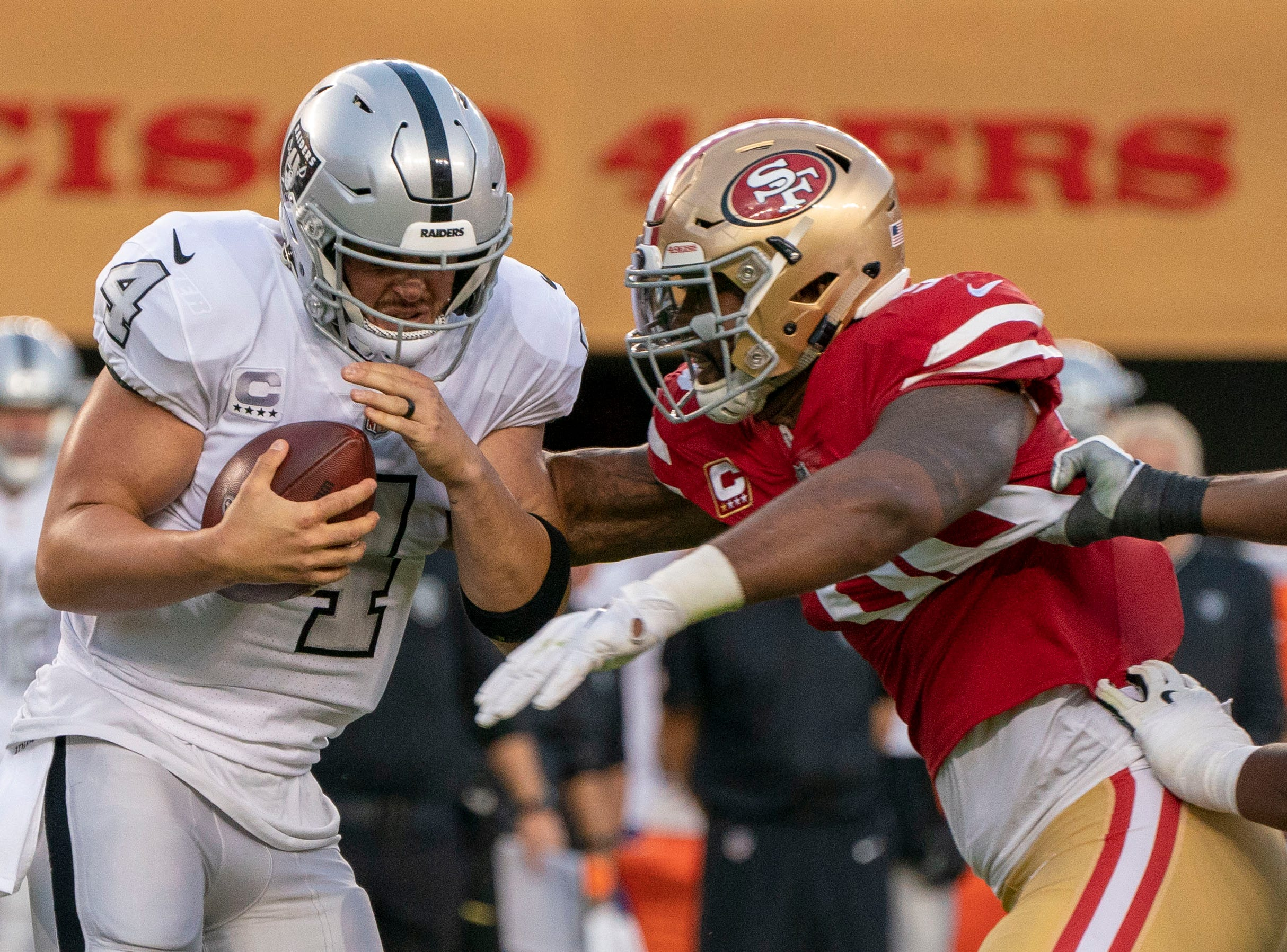 Oakland Raiders quarterback Derek Carr (4) is sacked by San Francisco 49ers defensive tackle DeForest Buckner (99) during the first quarter at Levi's Stadium.