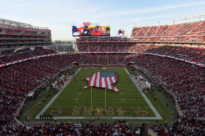 An American flag covers half the field during the national anthem prior to a game between the Oakland Raiders and the San Francisco 49ers at Levi's Stadium.
