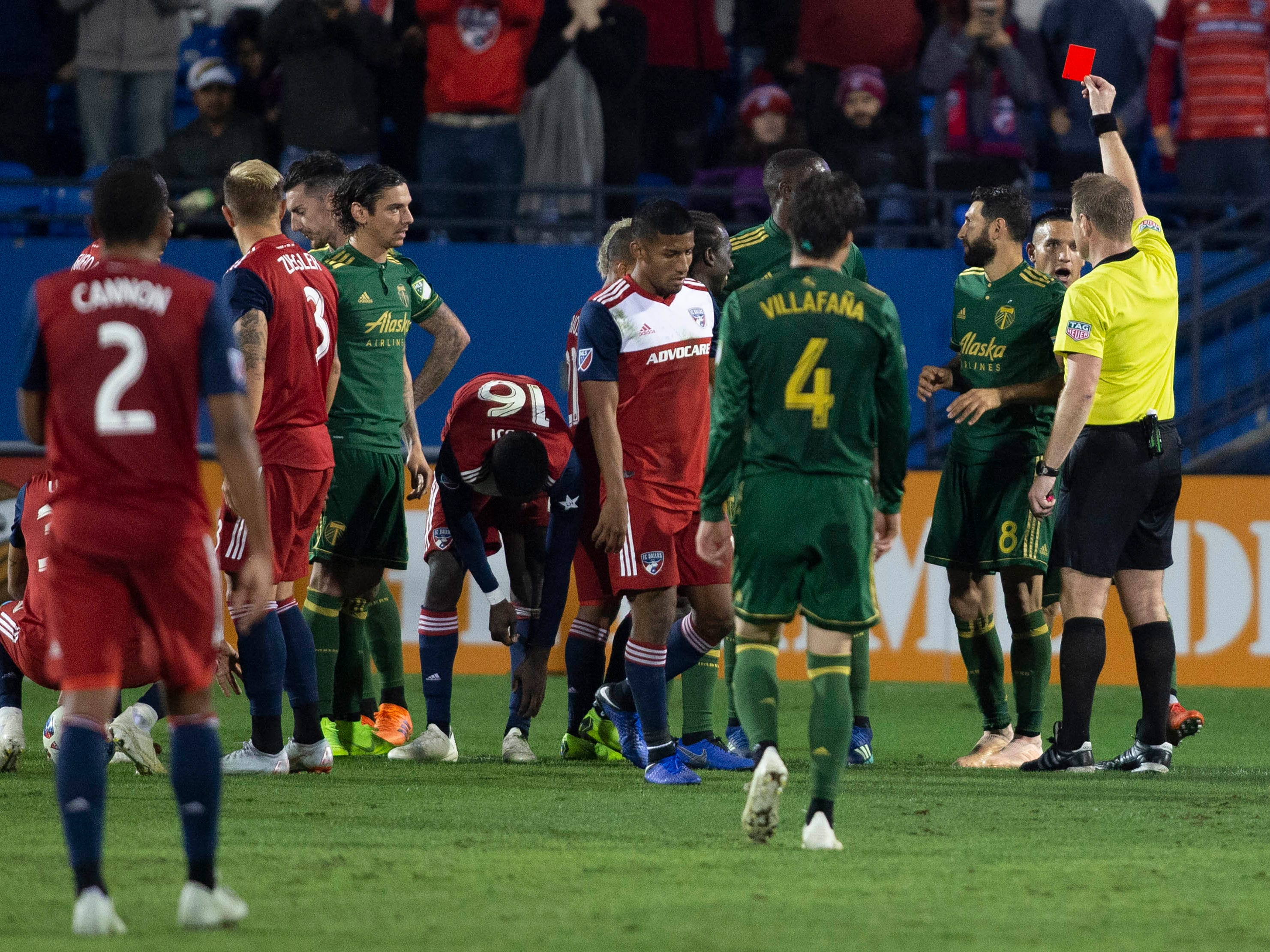 Referee Alan Kelly hands out a red card to Portland Timbers defender Larrys Mabiala in the second half against FC Dallas at Toyota Stadium.