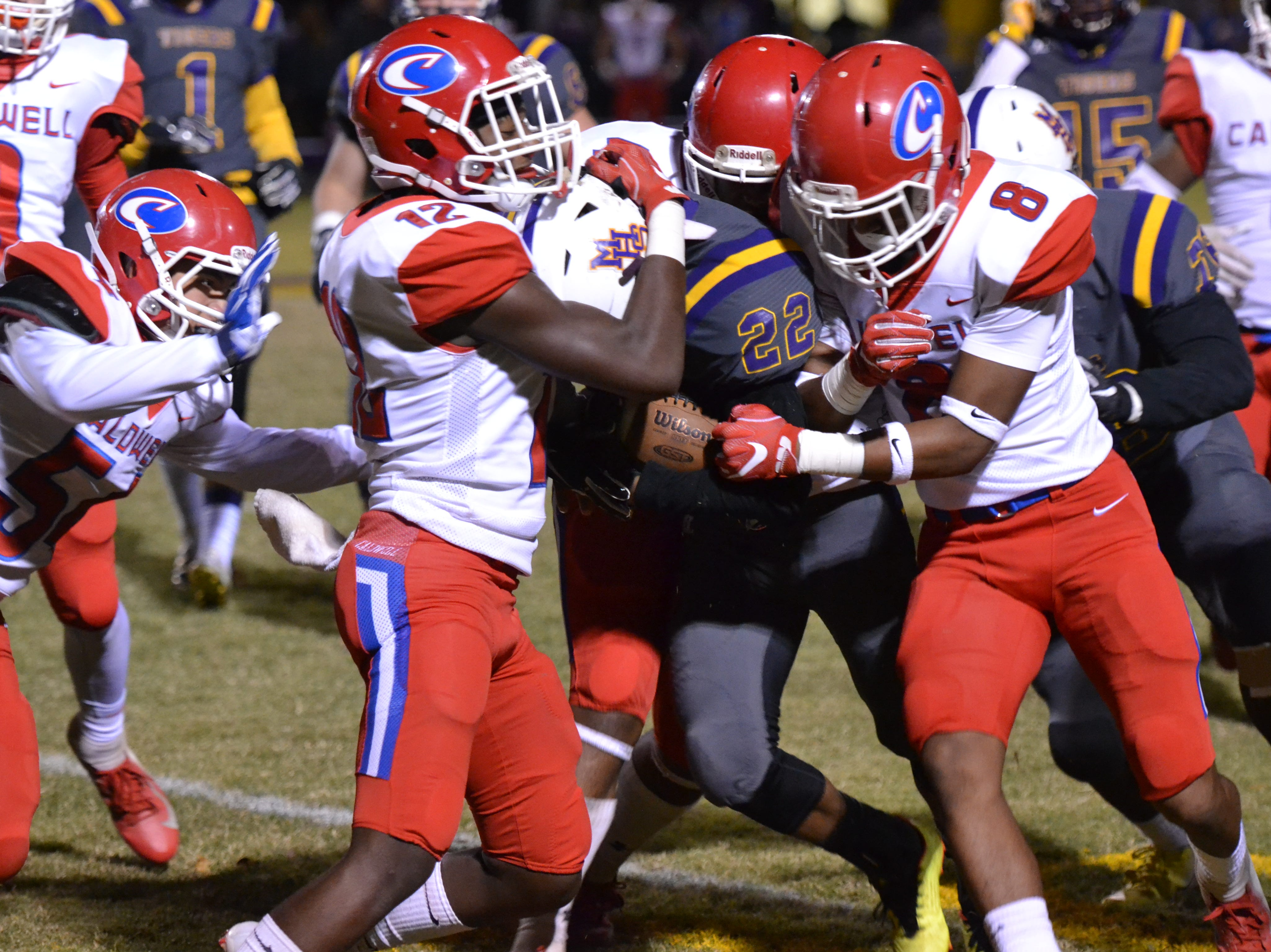 Caldwell defenders Eddie Turner (12) and Kenneth Harris (8) converge on Marksville's Kameron Washington (22). Marksville and Caldwell met in the regular season finale Friday night with Caldwell edging Marksville 13-8.