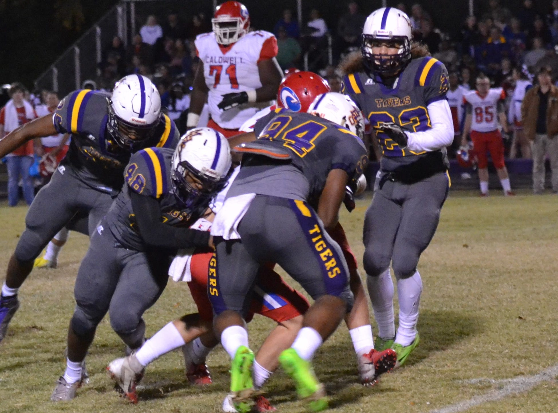 Tiger defenders Al Shamar Martin (48) and Triston Jacobs (94) smother the Caldwell runner. Marksville and Caldwell met in the regular season finale Friday night with Caldwell edging Marksville 13-8.