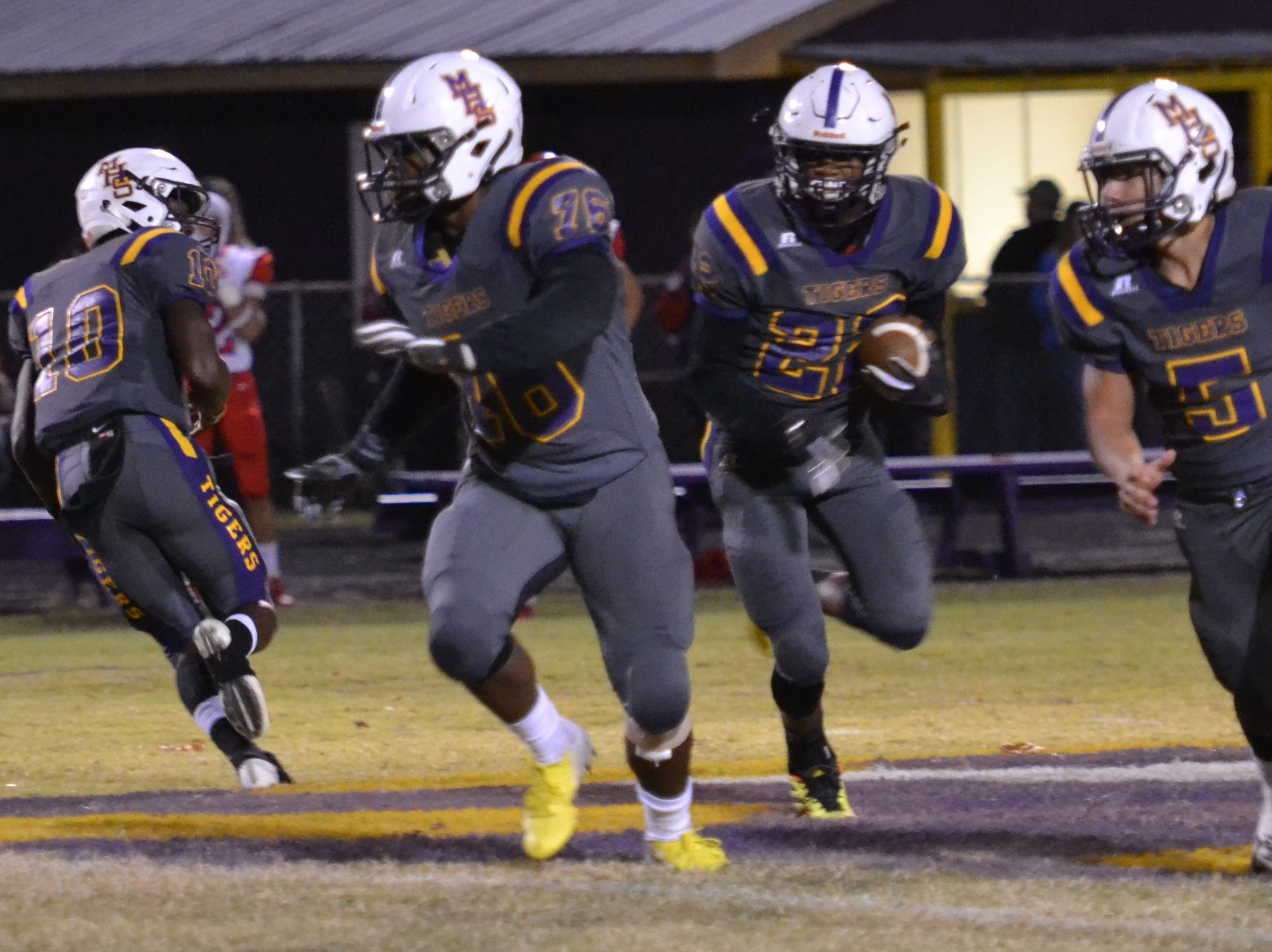 Tiger running back Kameron Washington  (22) gets the ball and has blockers Leonard Sampson (76) and Bryce Moseley (5) to lead his way. Marksville and Caldwell met in the regular season finale Friday night with Caldwell edging Marksville 13-8.
