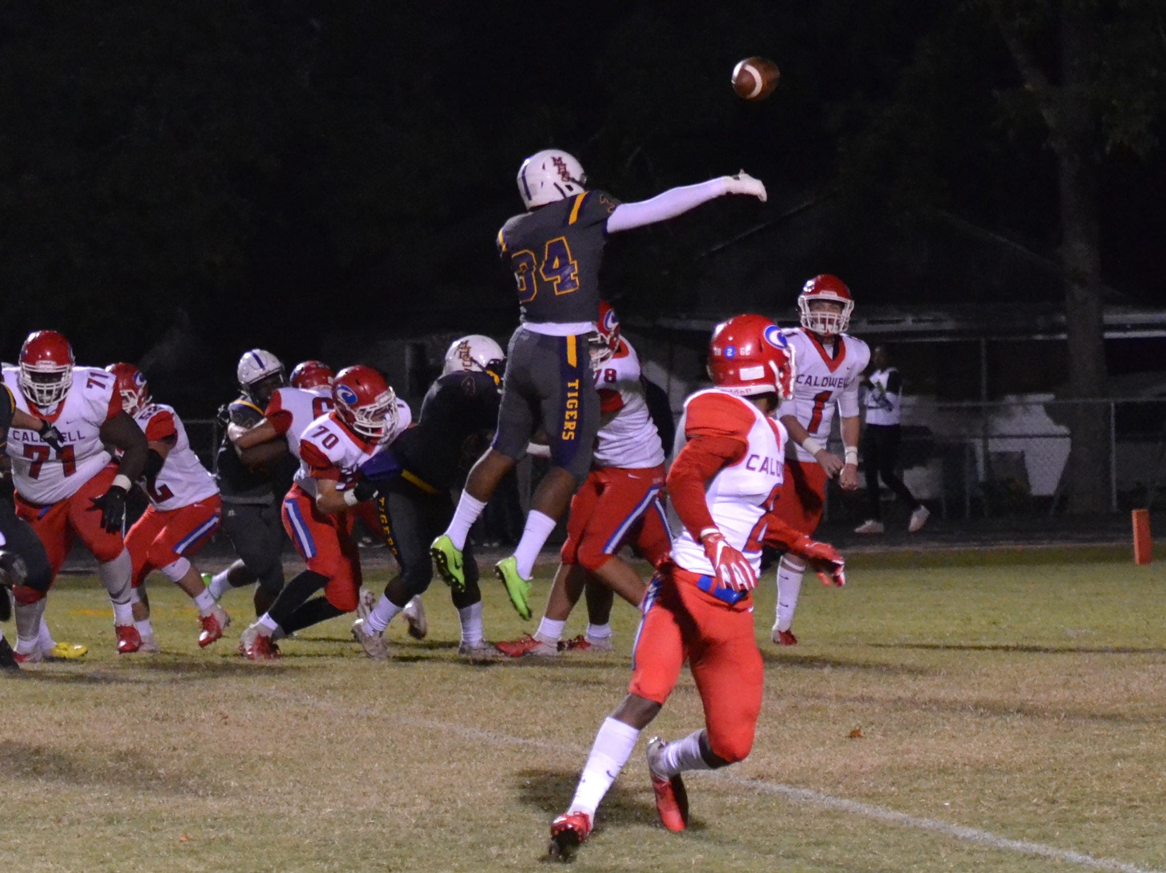 Tigers defender Chris Simon (34) leaps to try to deflect a pass by Caldwell quarterback Jaron Townsend (1). Marksville and Caldwell met in the regular season finale Friday night with Caldwell edging Marksville 13-8.
