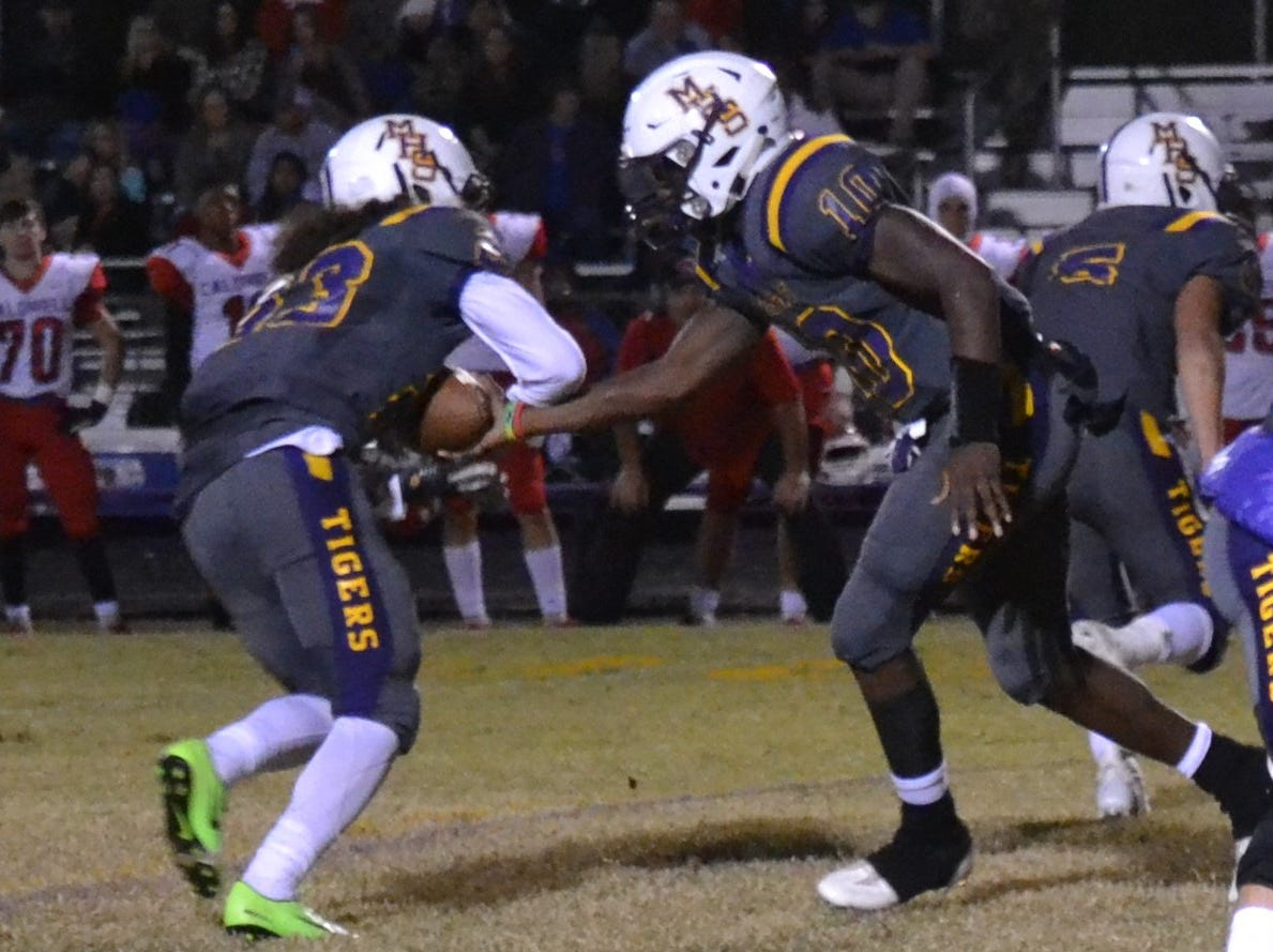 Jordan Batiste (23) takes a handoff from Tigers quarterback Daniel Miller (10). Marksville and Caldwell met in the regular season finale Friday night with Caldwell edging Marksville 13-8.
