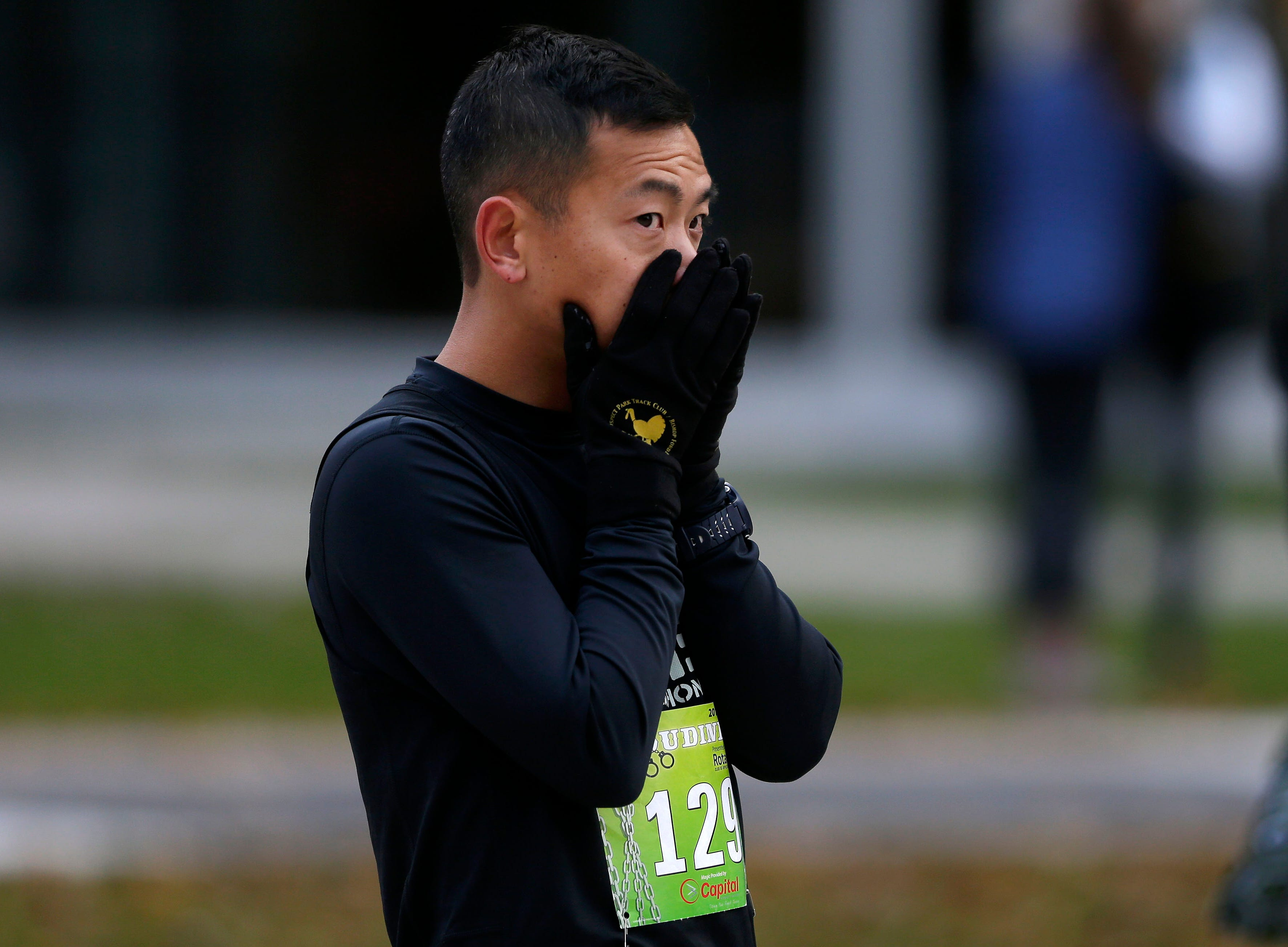 Philip Chiu stays warm before the start of the 4th annual Appleton Houdini 10K Saturday, November 3, 2018, in Appleton, Wis.