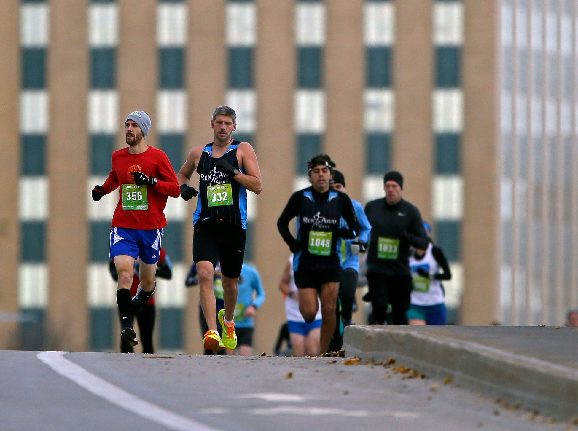 Runners cross the Oneida Street bridge as the 4th annual Appleton Houdini 10K takes place Saturday, November 3, 2018, in Appleton, Wis.