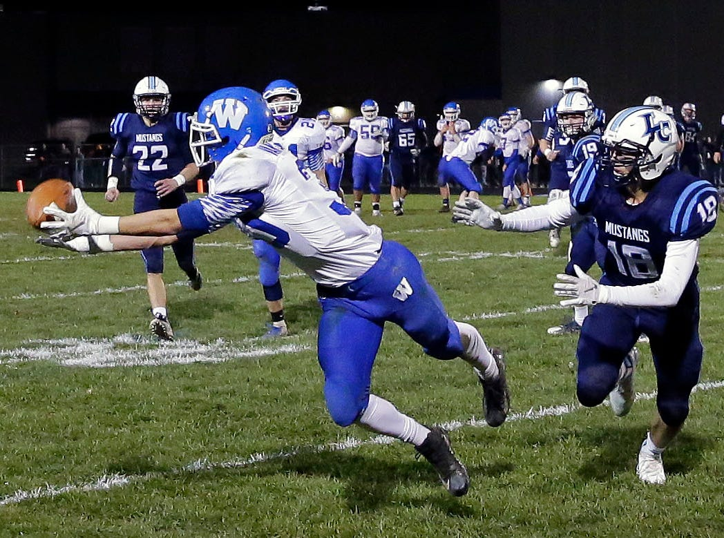 Jeremy Van Zeeland of Wrightstown stretches for the ball but doesn't make the catch while being defended by David Peeters of Llittle Chute in a WIAA Division 4 Level 3 playoff game Friday, November 2, 2018, at Fitzpatrick Field in Little Chute, Wis.Ron Page/USA TODAY NETWORK-Wisconsin