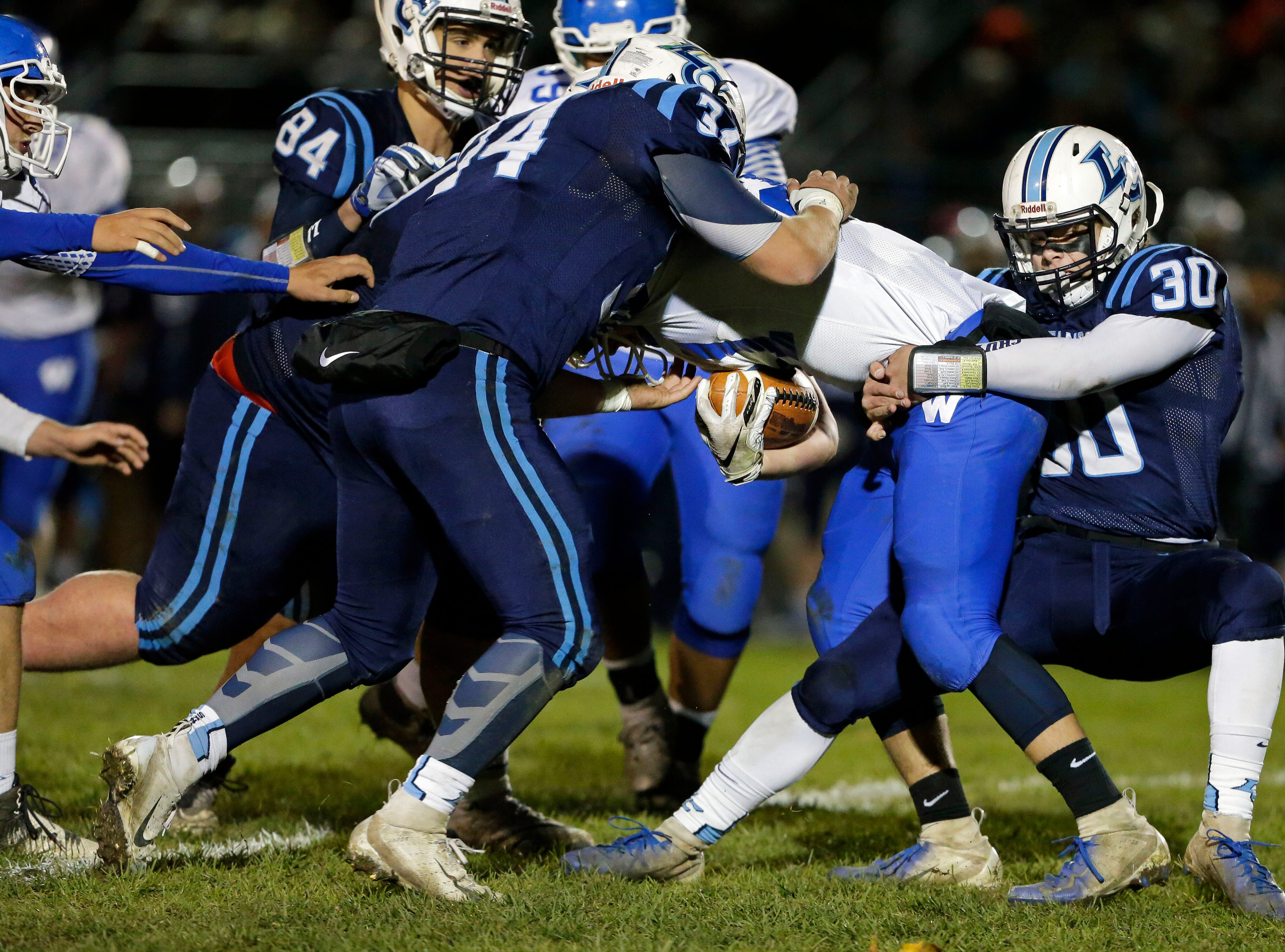 Thomas Mayefski (left) and Ryan Verstegen of Little Chute tackle Ben Jaeger of Wrightstown in a WIAA Division 4 Level 3 playoff game Friday, November 2, 2018, at Fitzpatrick Field in Little Chute, Wis.Ron Page/USA TODAY NETWORK-Wisconsin