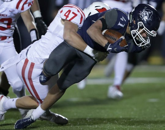 Bay Port's Isaiah Gash tries to break a tackle by Kimberly's Tristan Argall during Friday's game in Suamico.