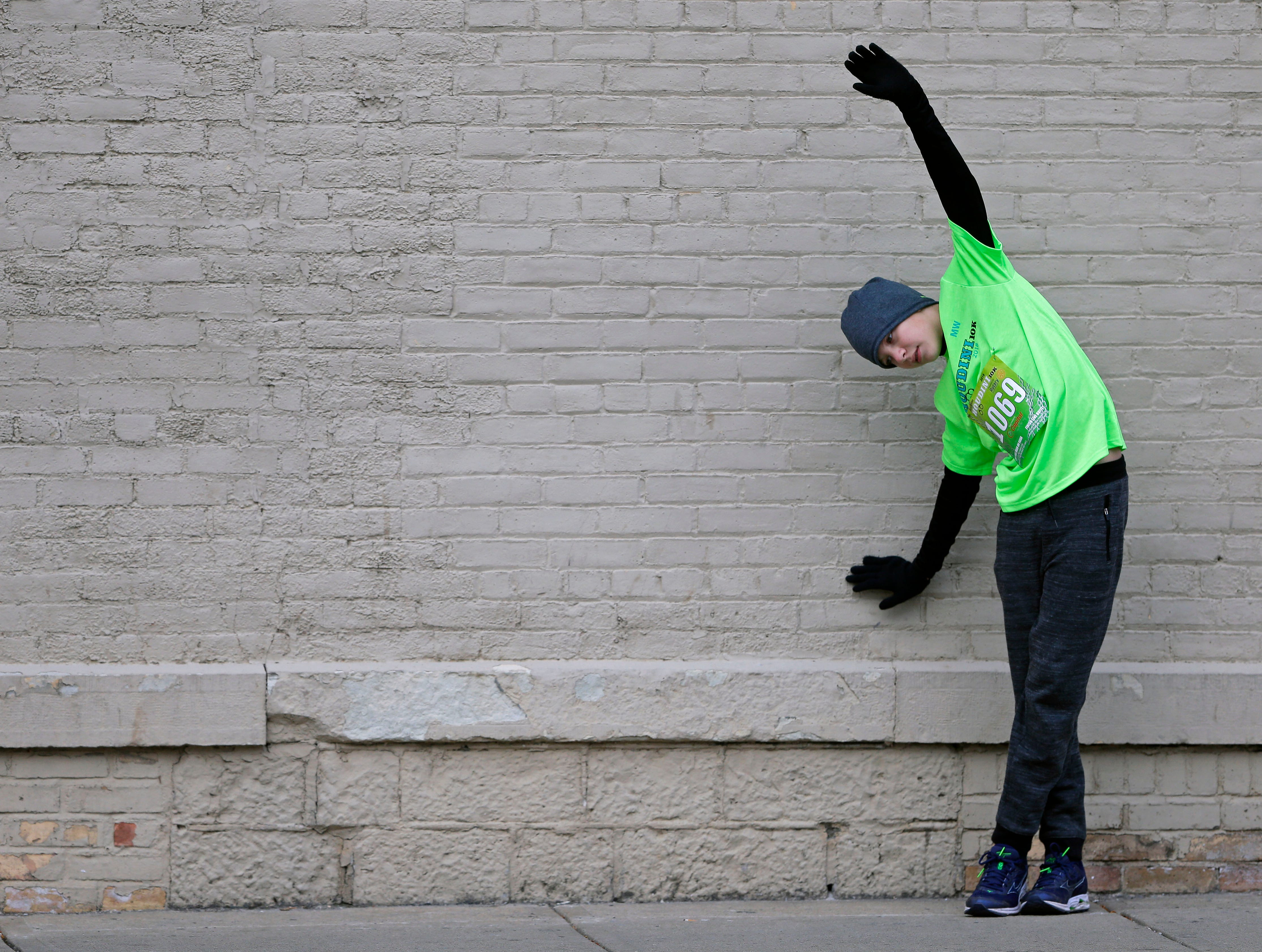 Simon Gavin stretches before the start of the 4th annual Appleton Houdini 10K Saturday, November 3, 2018, in Appleton, Wis.