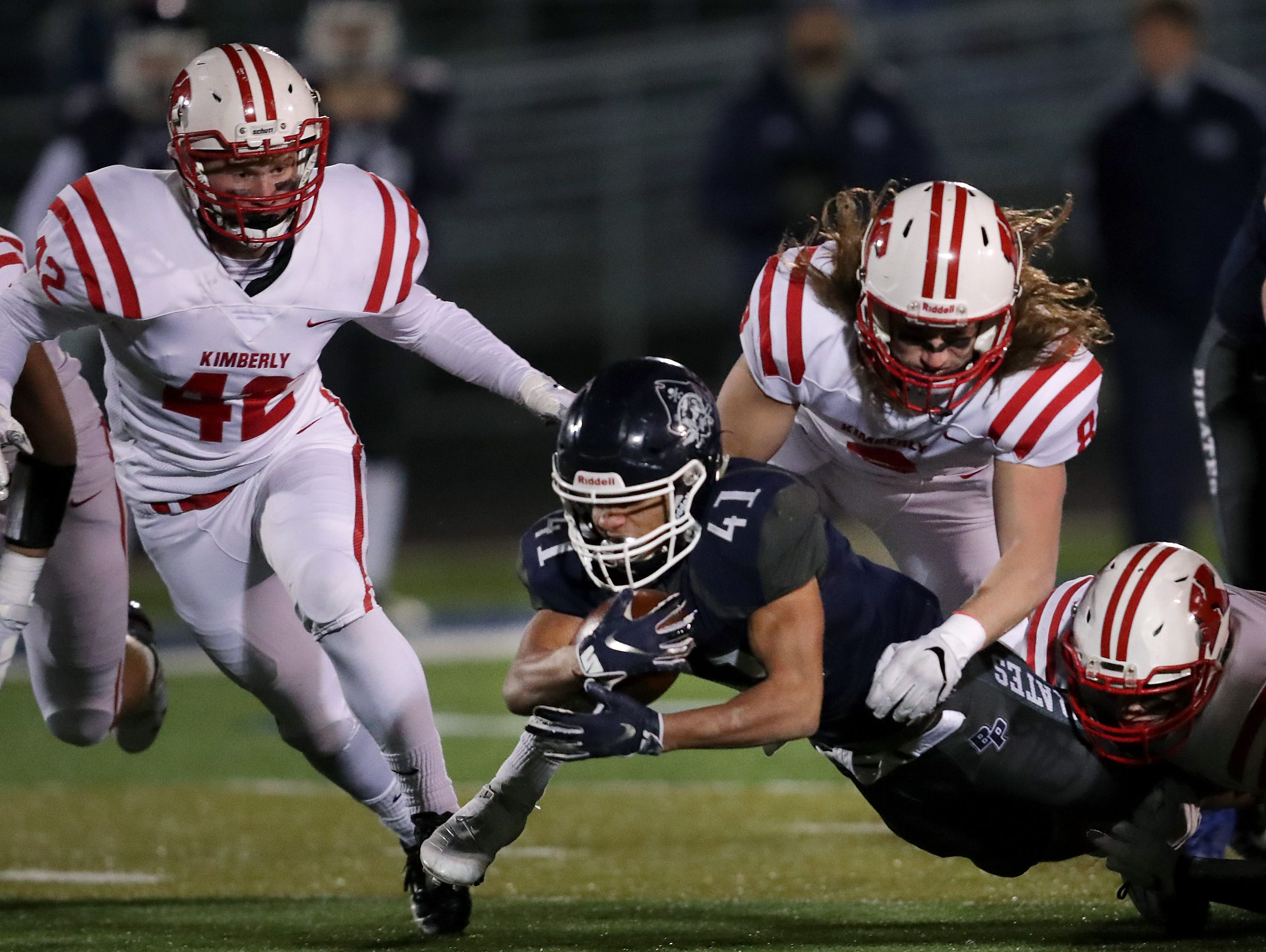 Kimberly High School's #42 Zach Arent, #8 Danny Kaltenbaugh and #22 Briar Barglind tackle Bay Port High School's #41 Isaiah Gash during their WIAA Division 1 state quarterfinal football game on Friday, November 2, 2018, in Suamico, Wis.  Kimberly defeated Bay Port 38 to 20. Wm. Glasheen/USA TODAY NETWORK-Wisconsin.