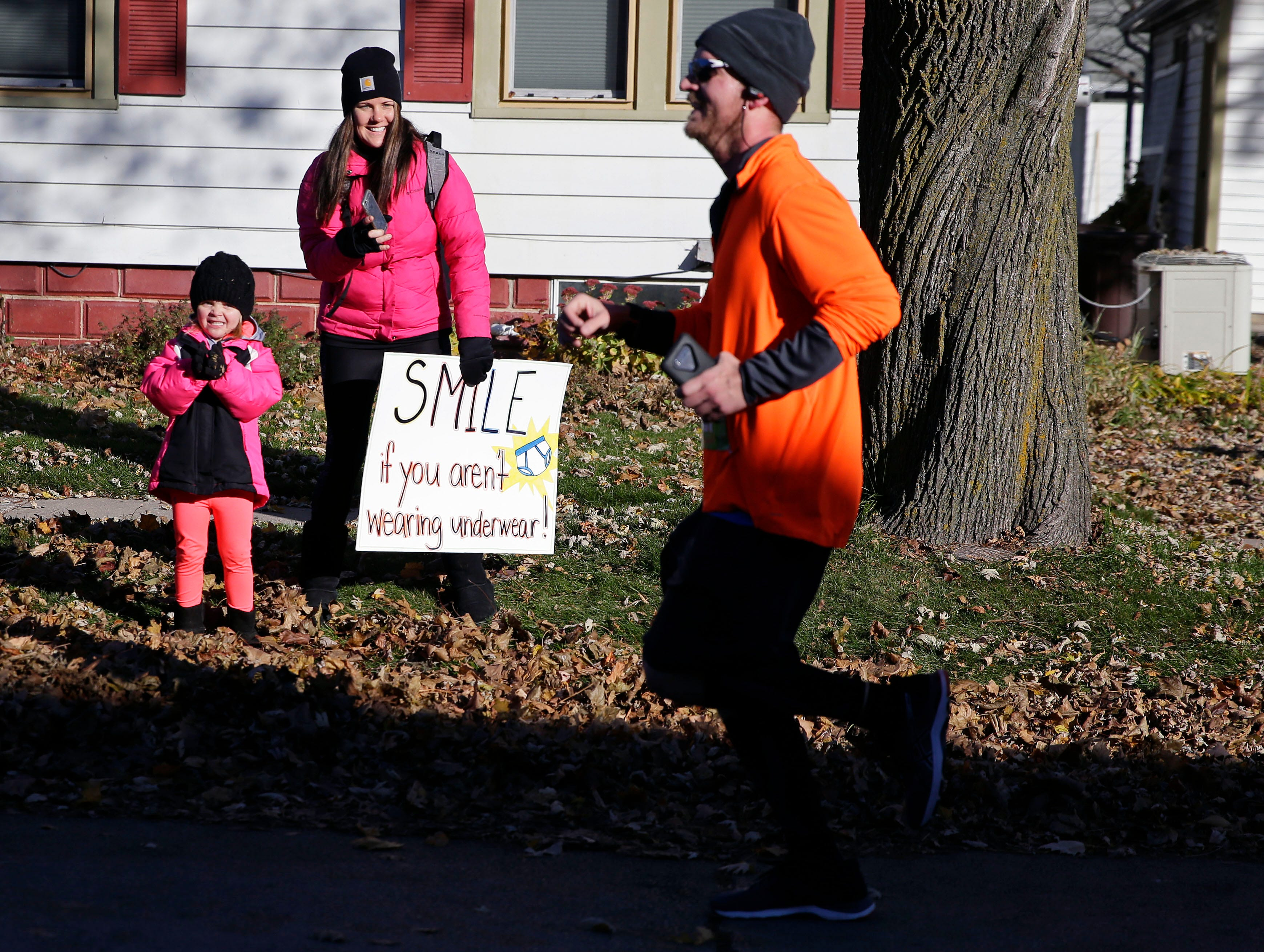 Kinsley Maas (left) and Liz Walker cheer for Keith Maas near the finish of the 4th annual Appleton Houdini 10K Saturday, November 3, 2018, in Appleton, Wis.