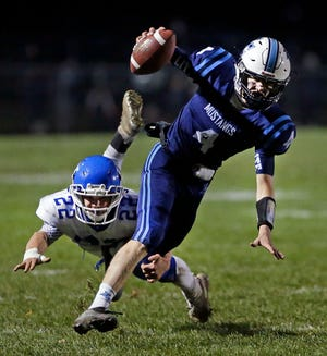 Quarterback Noah Mueller of Little Chute is tripped up by Walker Vande Hey of Wrightstown in a WIAA Division 4 state quarterfinal football game Friday in Little Chute.