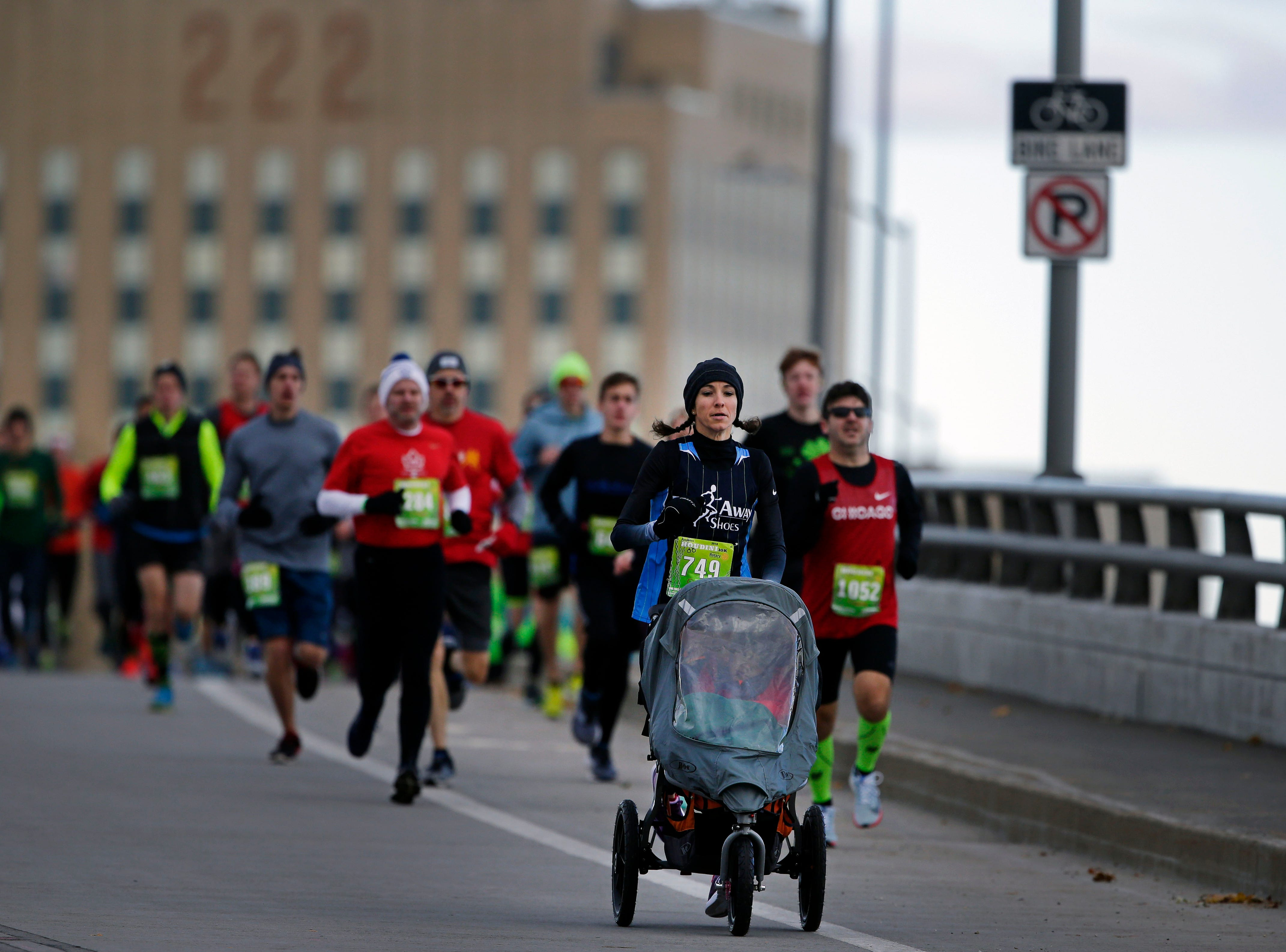 Laura Schmitz tackles the run with an addition as runners cross the Oneida Street bridge during the 4th annual Appleton Houdini 10K Saturday, November 3, 2018, in Appleton, Wis.