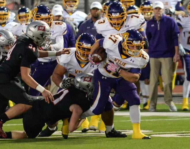 Wylie's Bailey Hicks (27) drags a Lubbock-Cooper defender for a few yards while running the ball before being brought down during the game Friday, Nov. 2, 2018, at Pirate Stadium in Woodrow, Texas.