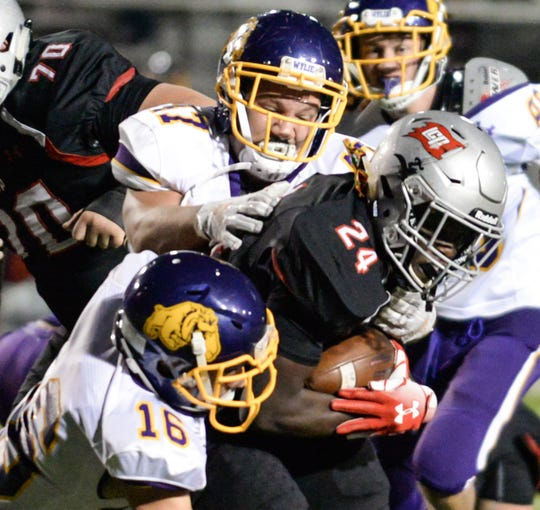 Wylie's Dayton Barnes (47) and Zach Corona (16) tackle Lubbock-Cooper's Tyler Hairston (24) during last week's game. Barnes and Corona helped lead the Bulldogs defensively and will try to slow down Plainview's rushing attack on Friday.