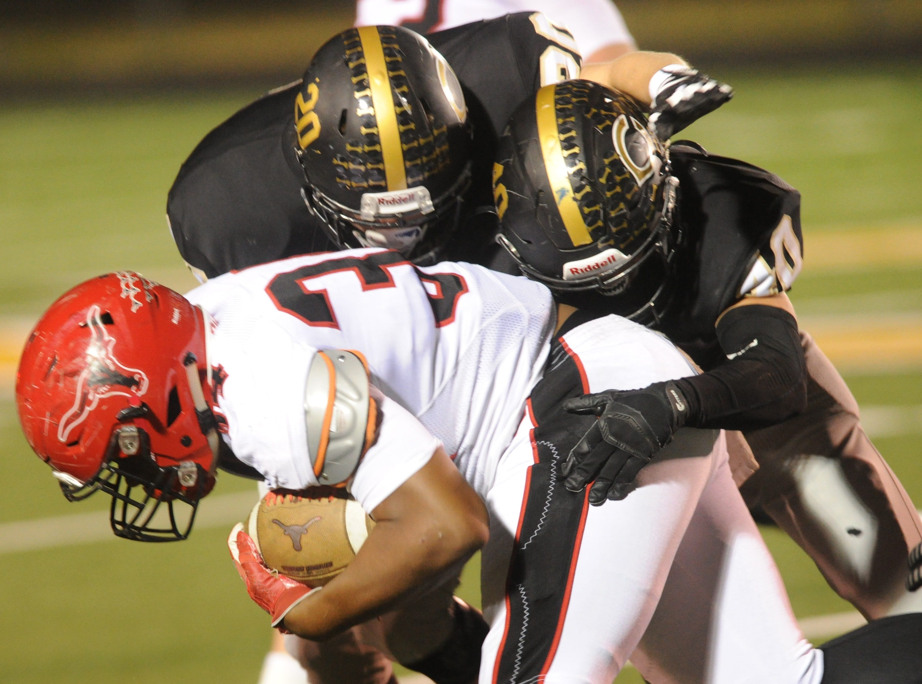 Clyde's Britten Brashear (20) and Bo Baker tackle Eastland running back Brandon Fielding during the first half of their District 3-3A Division I game Friday, Nov. 2, 2018, at Clyde. Eastland rallied from a 14-7 halftime deficit to beat the Bulldogs 28-14.