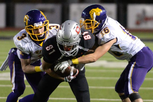 Wylie's Jaden Speegle (3) and Zach Corona (16) tackle Lubbock-Cooper's Ty Carter (81) during the game Friday, Nov. 2, 2018, at Pirate Stadium in Woodrow, Texas.