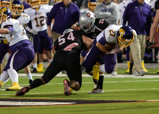 Wylie tailback Bailey Hicks (27) is tackled by Lubbock-Cooper's Jarred Gibson (54) and Rylan Wilcox (28) during last week's game. Hicks is one of 32 seniors playing his final game on Friday night against Plainview.