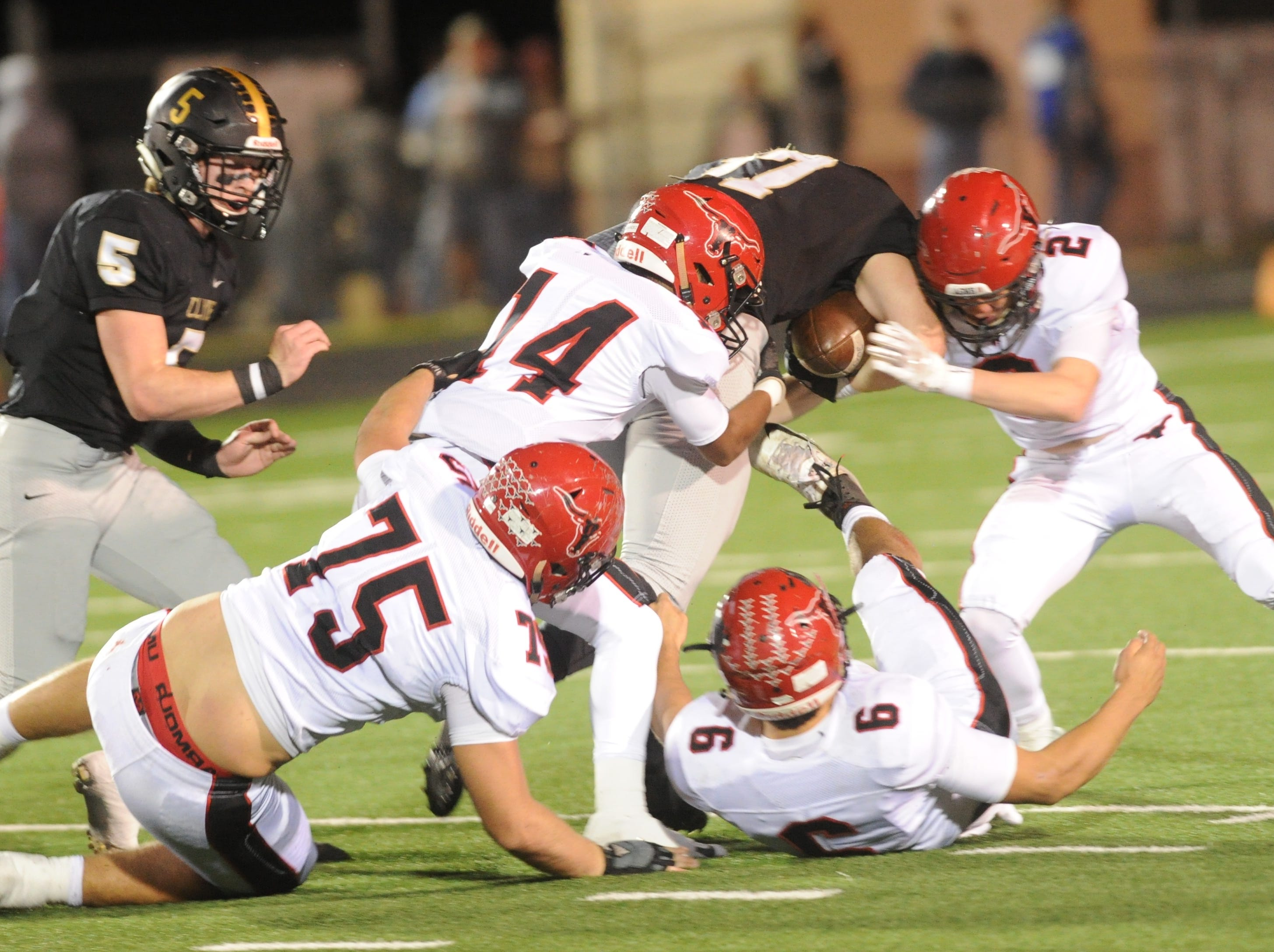 Eastland's Isaiah Hernandez (14), Zach Brown (2), Anthony Bonilla (6) and Dylan Green (75) try to bring down Clyde's Patyon Burton during the first half of their District 3-3A Division I game Friday, Nov. 2, 2018, at Clyde. Eastland rallied from a 14-7 halftime deficit to beat the Bulldogs 28-14.