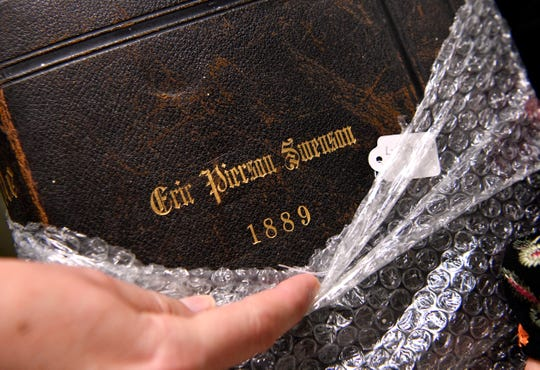 Jewellee Kuenstler, the curator for the Cowboy Country Museum in Stamford, pulls back the plastic protecting a family Bible on loan from the Swenson family whose ranches helped establish the city.