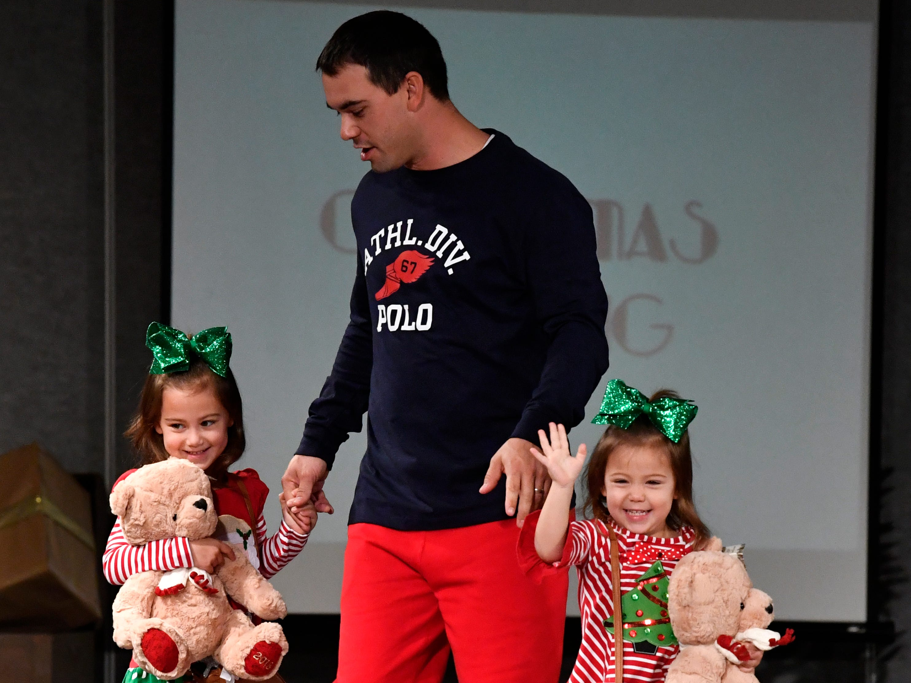 Justin Tabor escorts his daughters Breland (5, left) and Paisley, 3, during the fashion show luncheon at Friday's Junior League of Abilene Christmas Carousel Nov. 2, 2018. The holiday shopping event at the Abilene Convention Center ends Sunday.