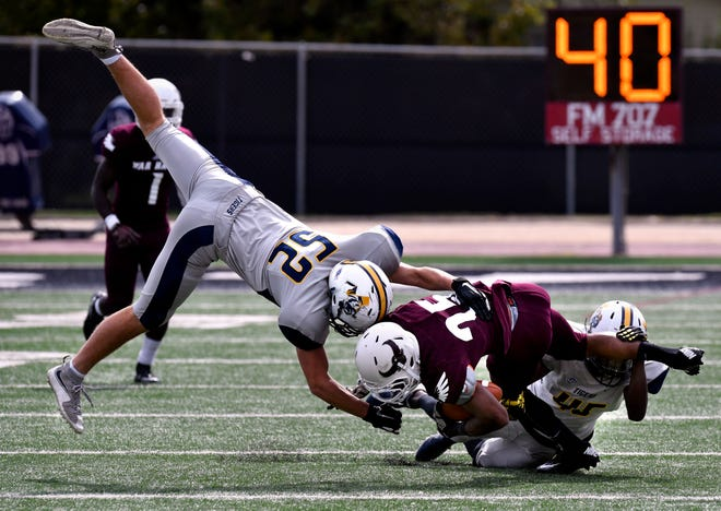 War Hawks wide receiver Spencer Knox is tackled by East Texas Baptist linebacker  Garrett Lybrand (left) and safety Derick Holt during Saturday's game at McMurry University Nov. 3, 2018.