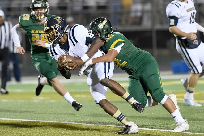 Reynolds' Marc Golden takes down Roberson's Devin Credle during their game at Reynolds High School on Nov. 2, 2018. The Rockets defeated the Rams 55-28.