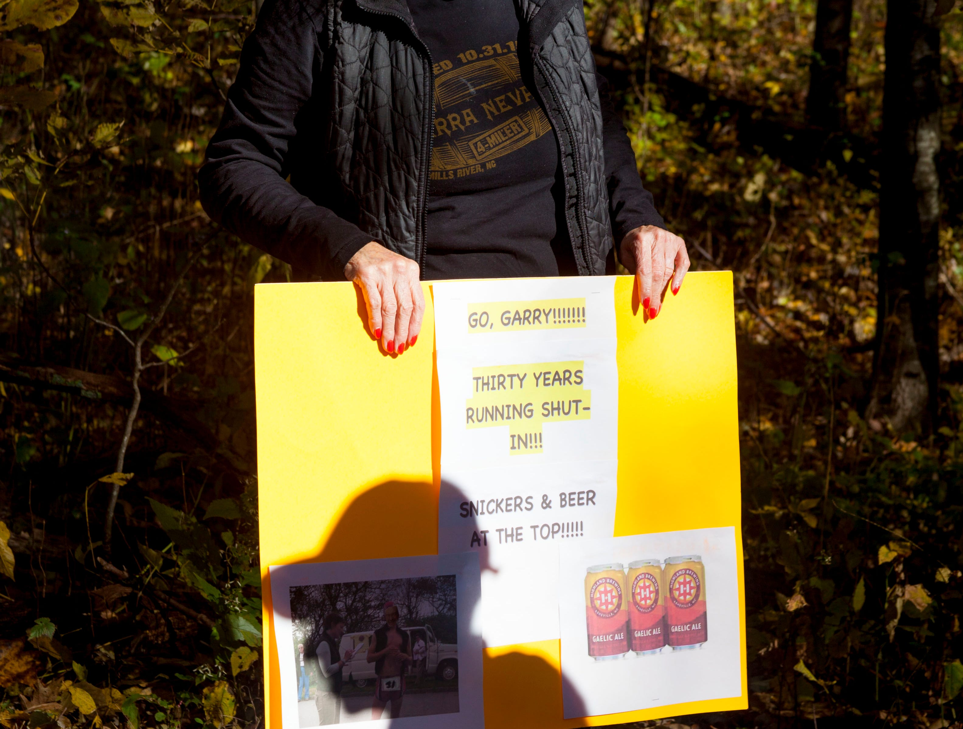 "Gail Sherman holds a sign of support for her husband Garry, who has raced in the past 30 Shut-In Ridge Trail Races. The Shut-In Ridge Trail Race for 2018 took place Saturday, Nov. 3. The race along the Blue Ridge Parkway began at the North Carolina Arboretum and ended at Mount Pisgah. The 17.8-mile route is touted as ""one of Asheville's most iconic and grueling trails."" Learn more at shutintrailrace.com."