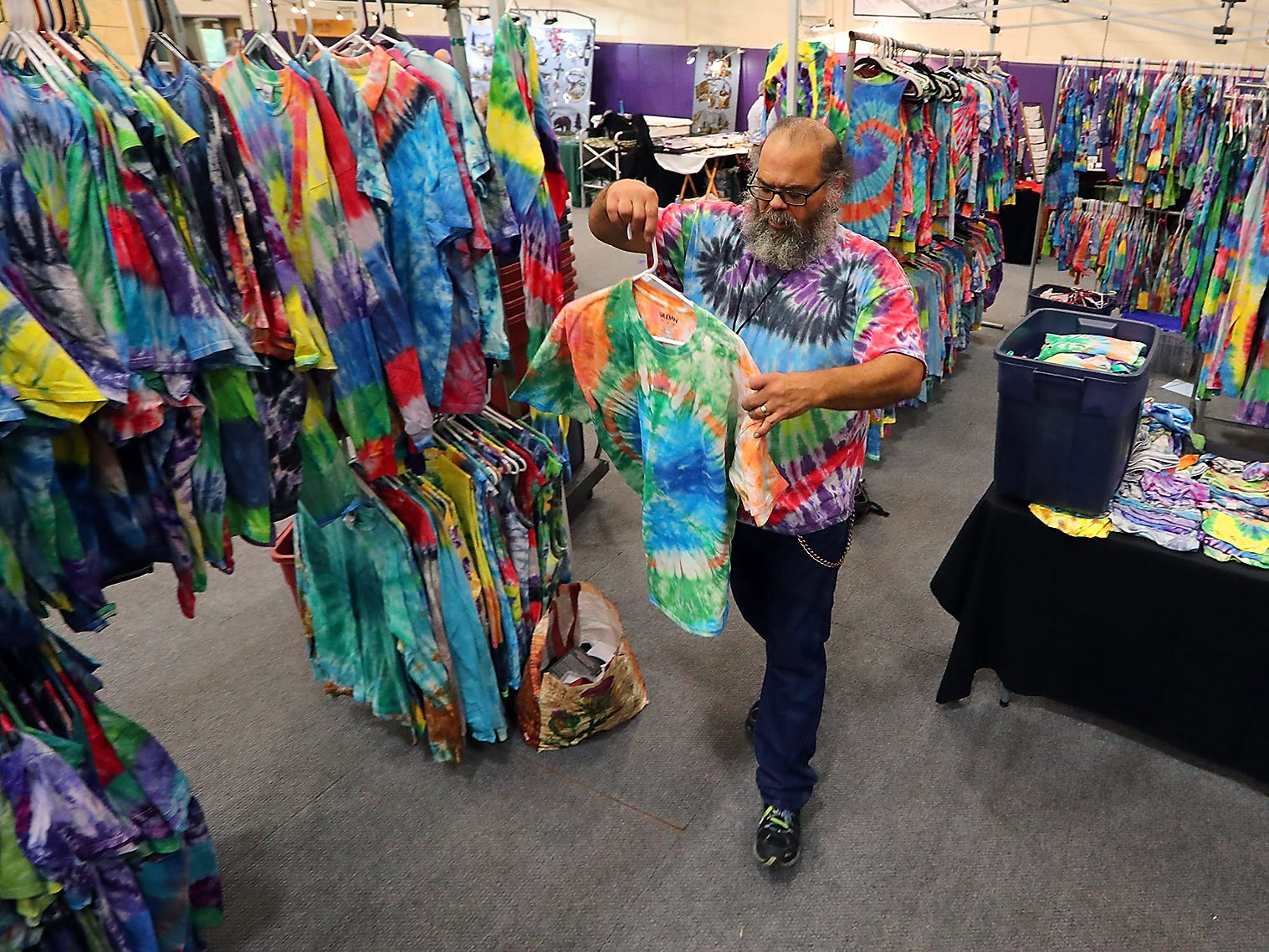Peter Simon, of Everett, hangs up a tie-dyed shirt in his To Dye For booth during the NK Holiday Fest at North Kitsap High School Saturday. The annual event kicks off the holiday bazaar season featuring crafts, arts, food, gifts and more. The event continues Sunday from 11 a.m. until 4 p.m. Admission is $5, but children 10 and younger are free.