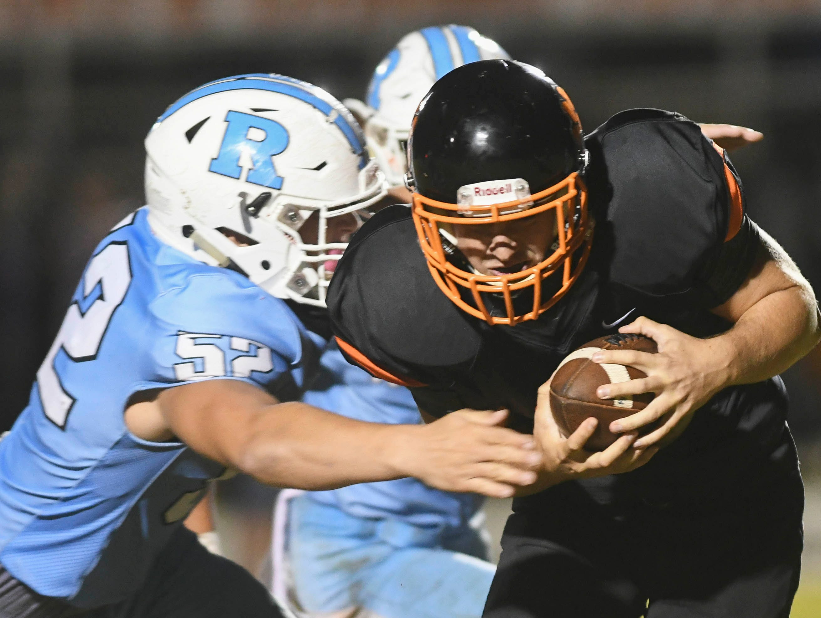 Cocoa punter Alex Petruzzello is smothered by Jordan Love and Terrance Griffin of Rockledge during Friday's game.