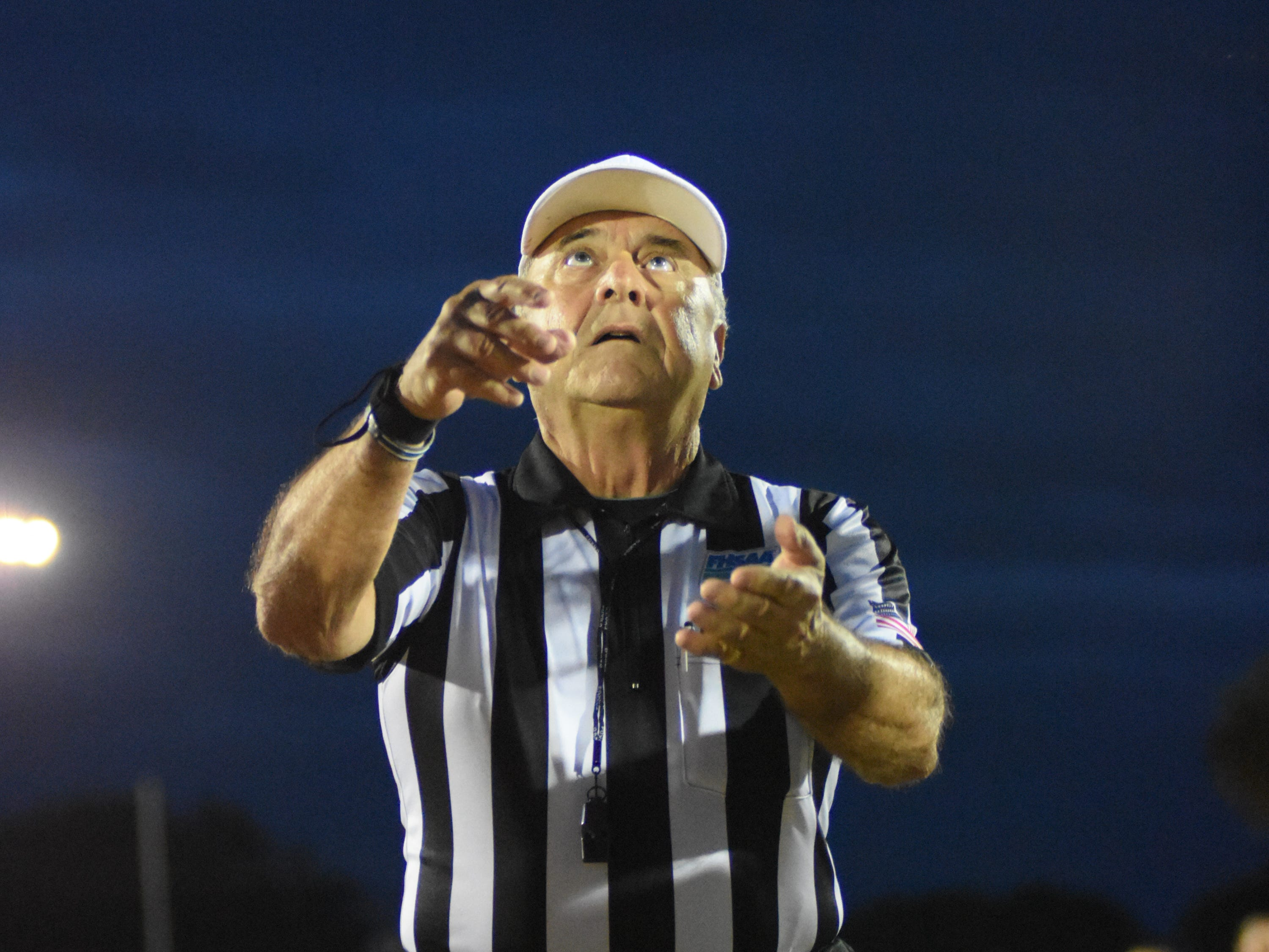 Referee Larry Torchia tosses the coin.