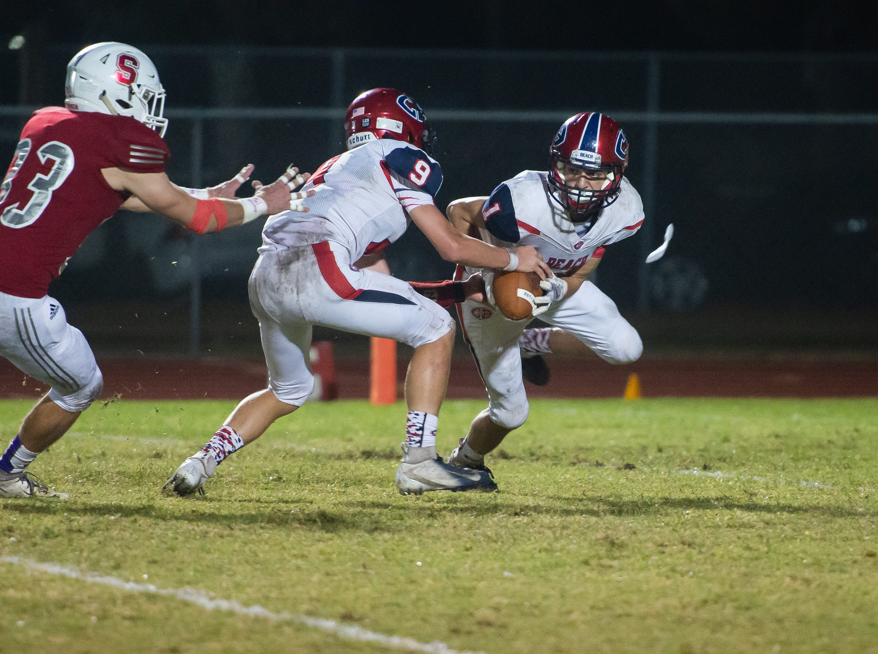 Cocoa Beach's Thomas Nargi hands the ball to Ryan Tsarnas during the first half against Satellite High.