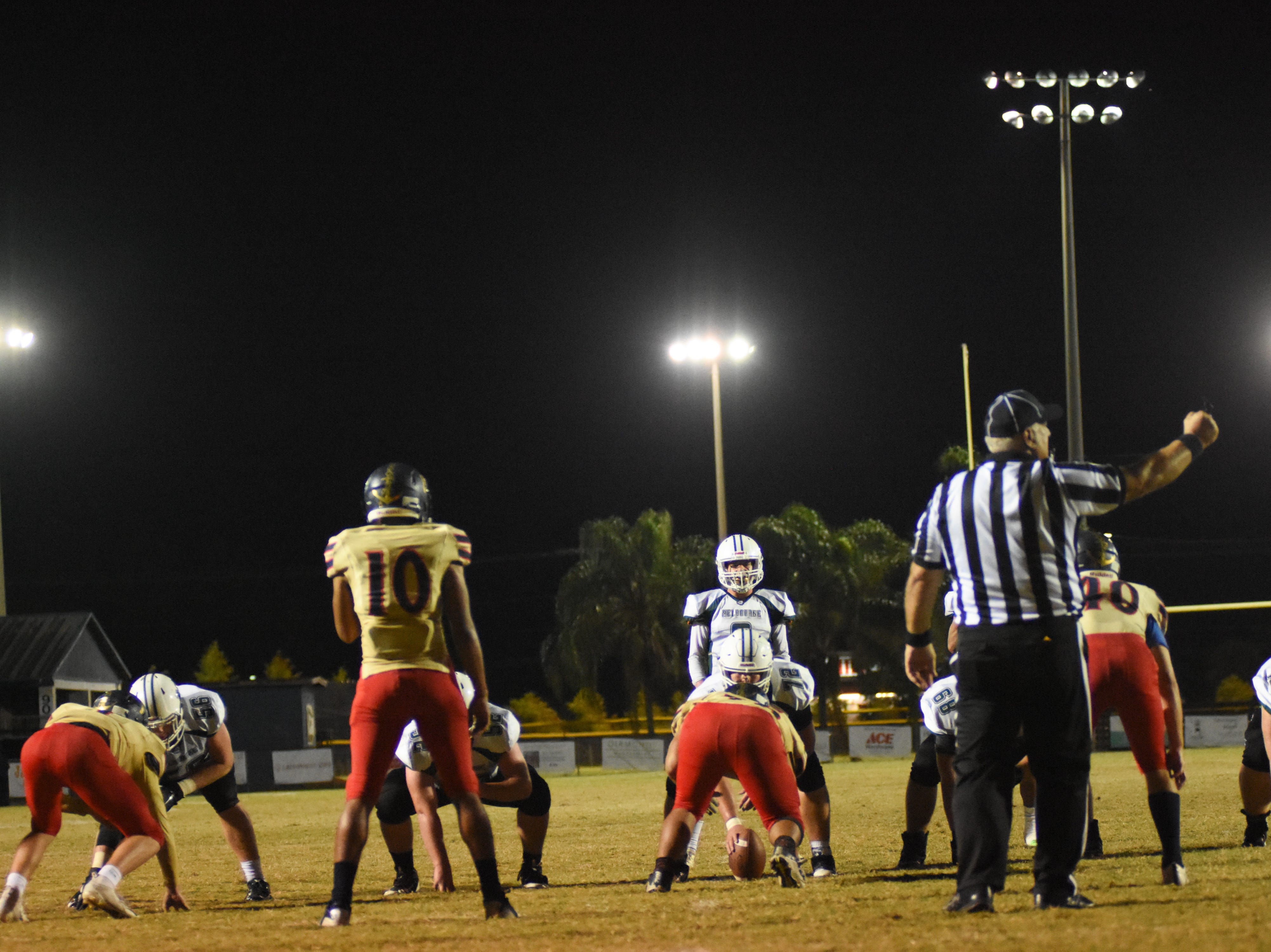 Melbourne's offense gets set by the goal line under the lights.