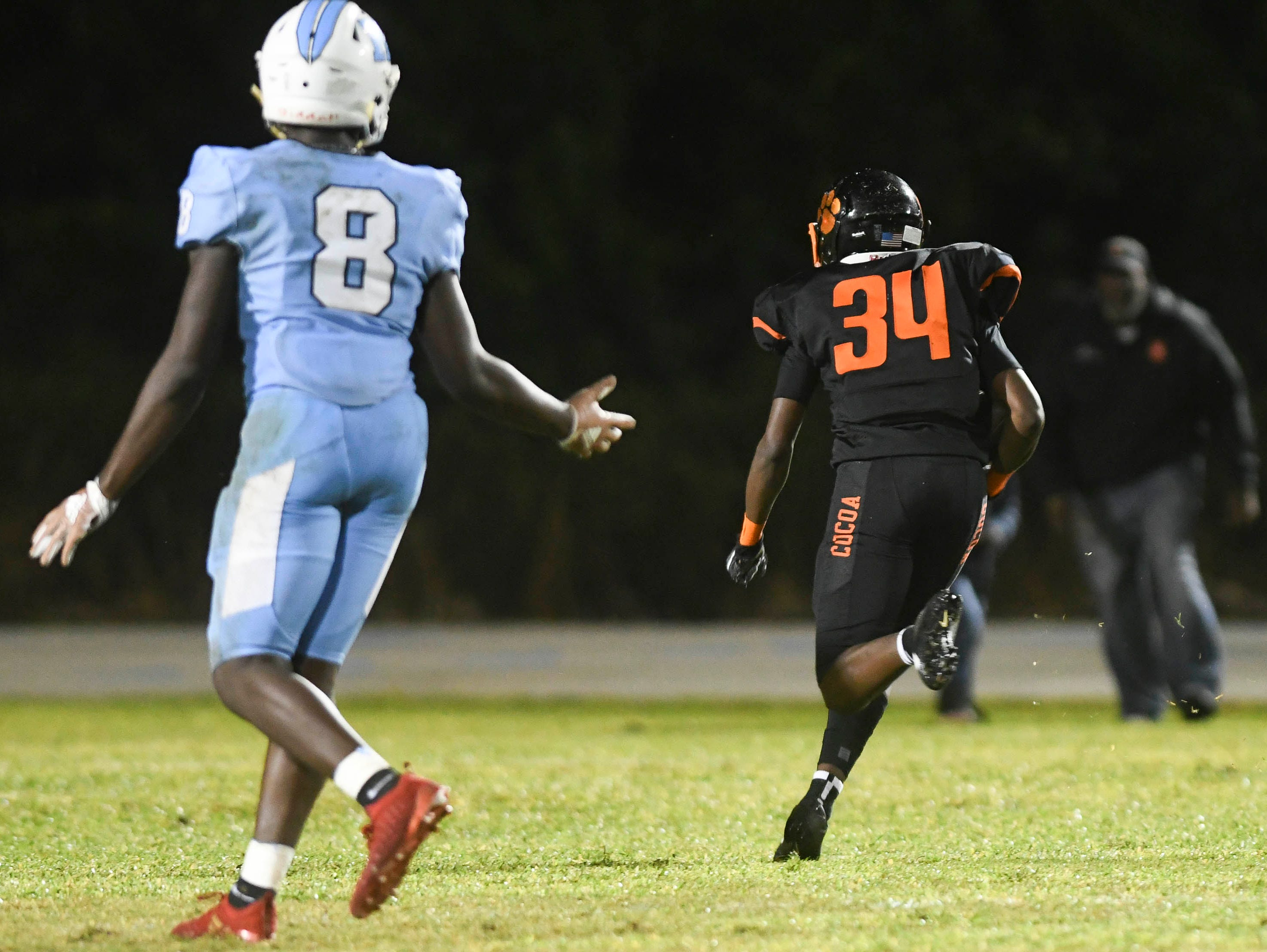 OC Brothers of Rockledge watches as Cocoa's OC Ross(34) returns an interception to the three yard line during Friday's game.