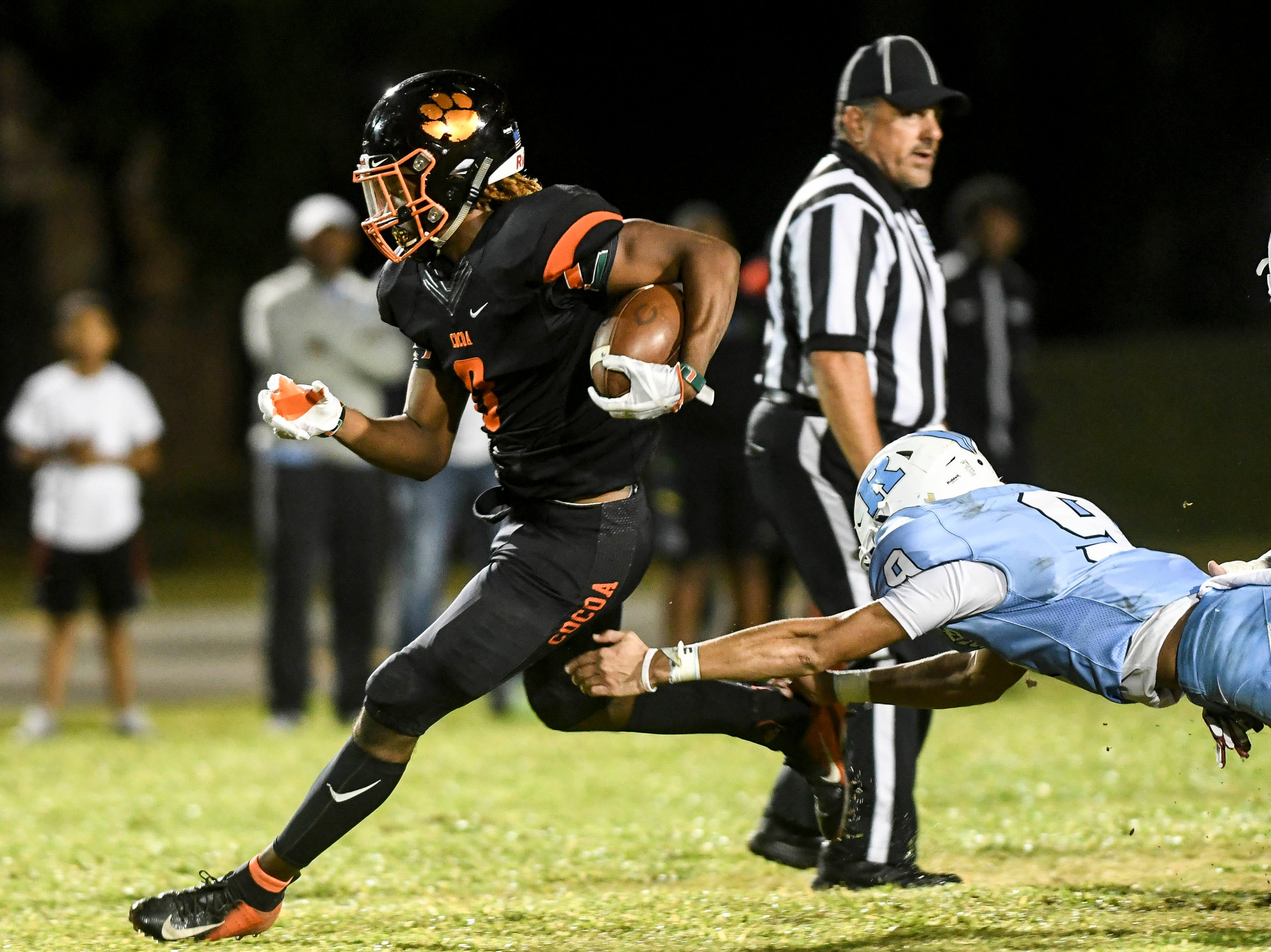 Cocoa's Caziah Holmes tries to get around the tackle of Terrance Griffin of Rockledge during Friday's game.
