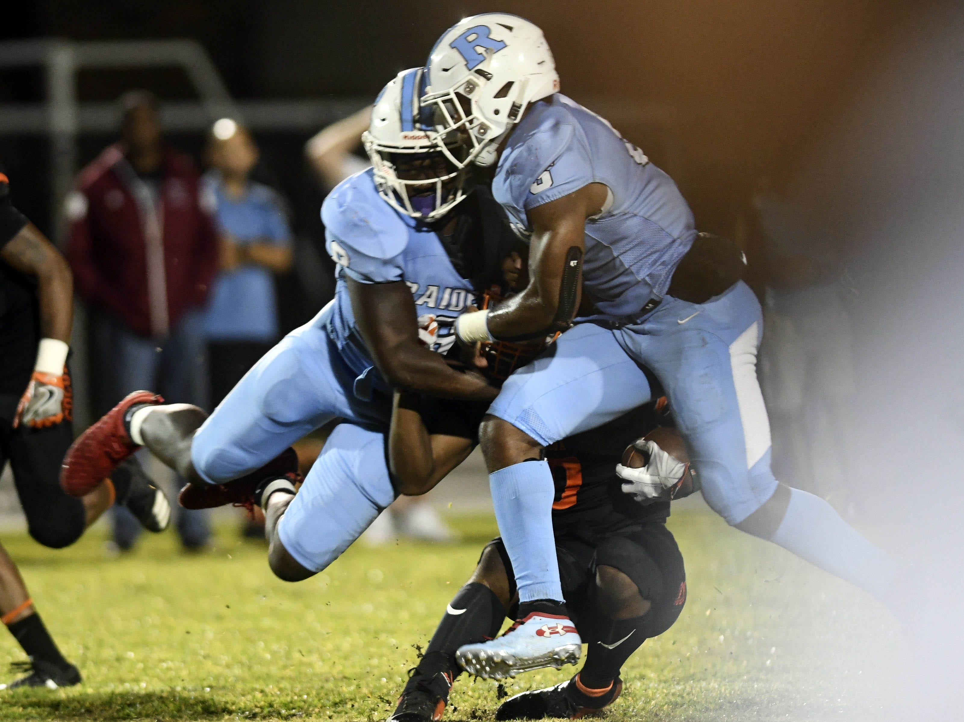 Caziah Holmes of Cocoa is tackled by OC Brothers and Jalen Mitchell during Friday's game.