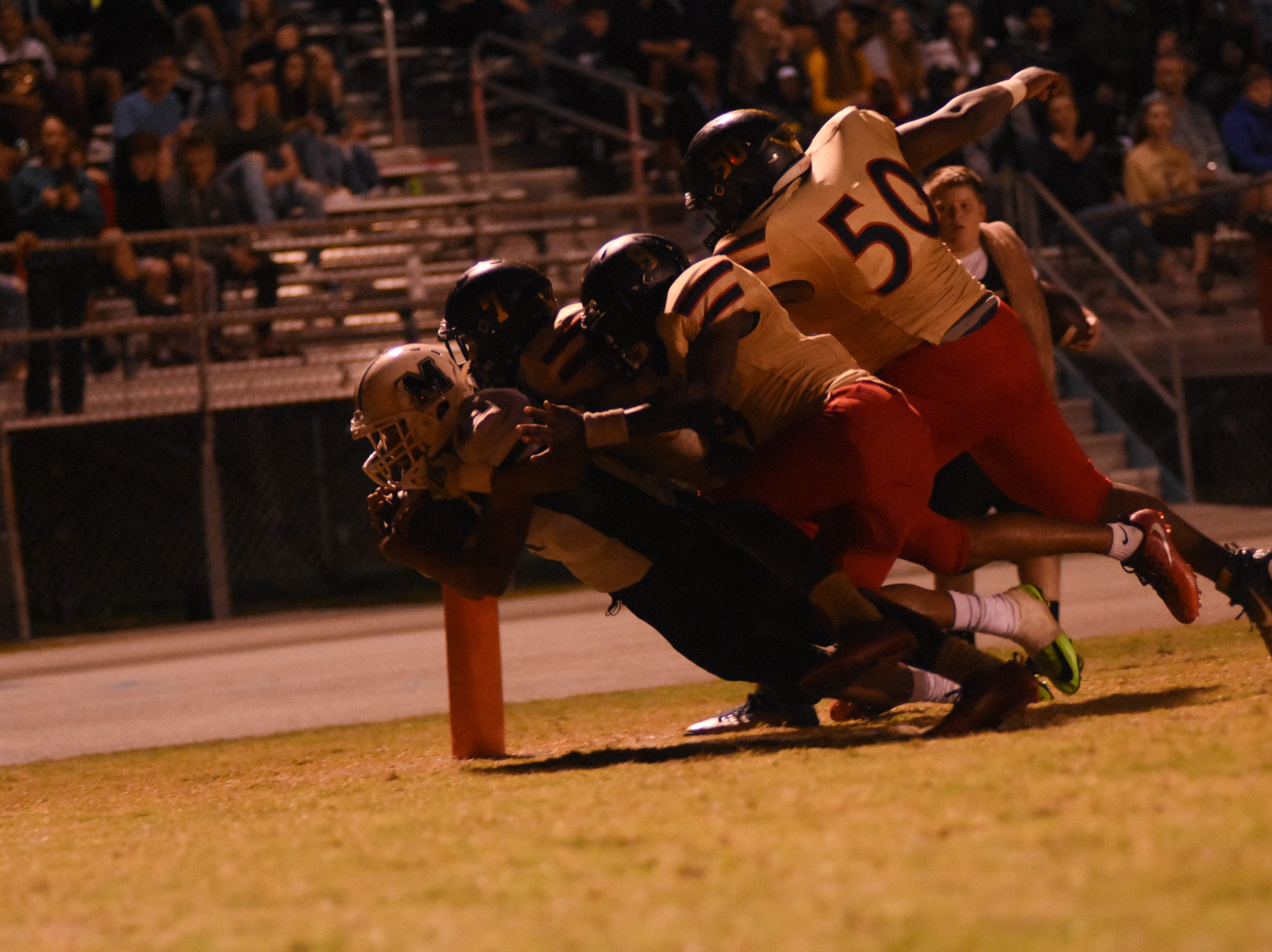 Antonio Wright Jr. (7) is brought down by three Commodores just inside the end zone.