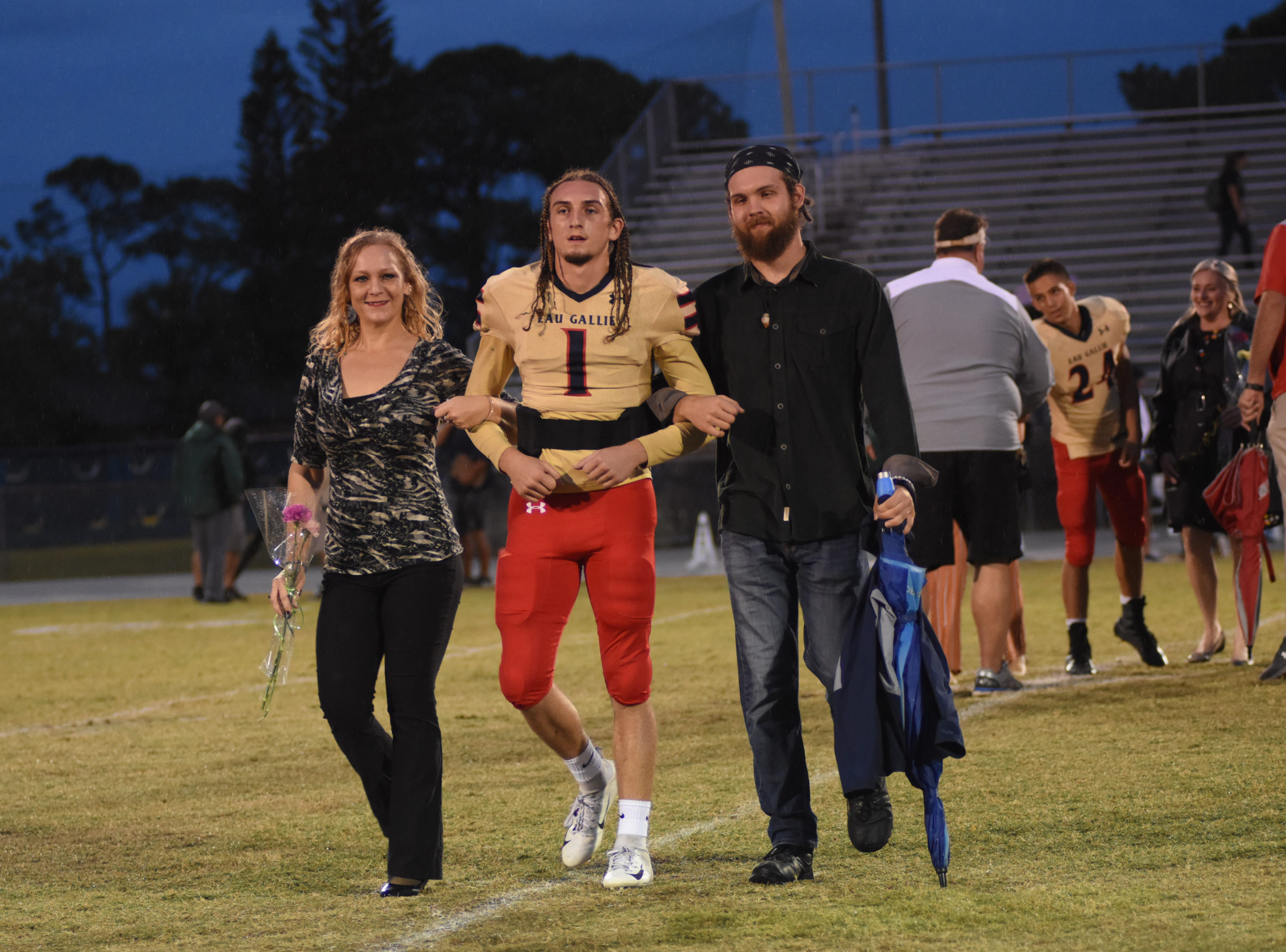 Eau Gallie's Hunter Smith (1) walks down mid field with his parents to celebrate Senior Night.