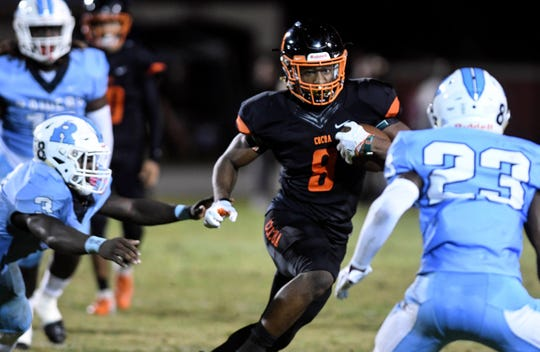 Caziah Holmes of Cocoa (8) tries to get past Rockledge defenders Ladrius Tennison (3) and Maurice Griffin  during Friday's game.
