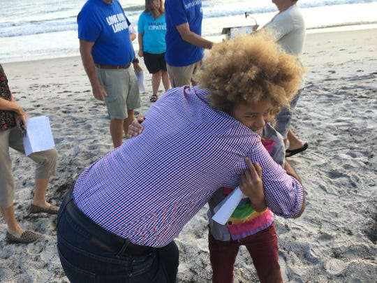 Sanjay Patel, a Democrat running for the U.S. House of Representative District 8 seat, hugs 11-year-old environmental activist, Levi Draheim during a campaign event Saturday at Pelican Beach Park in Satellite Beach.