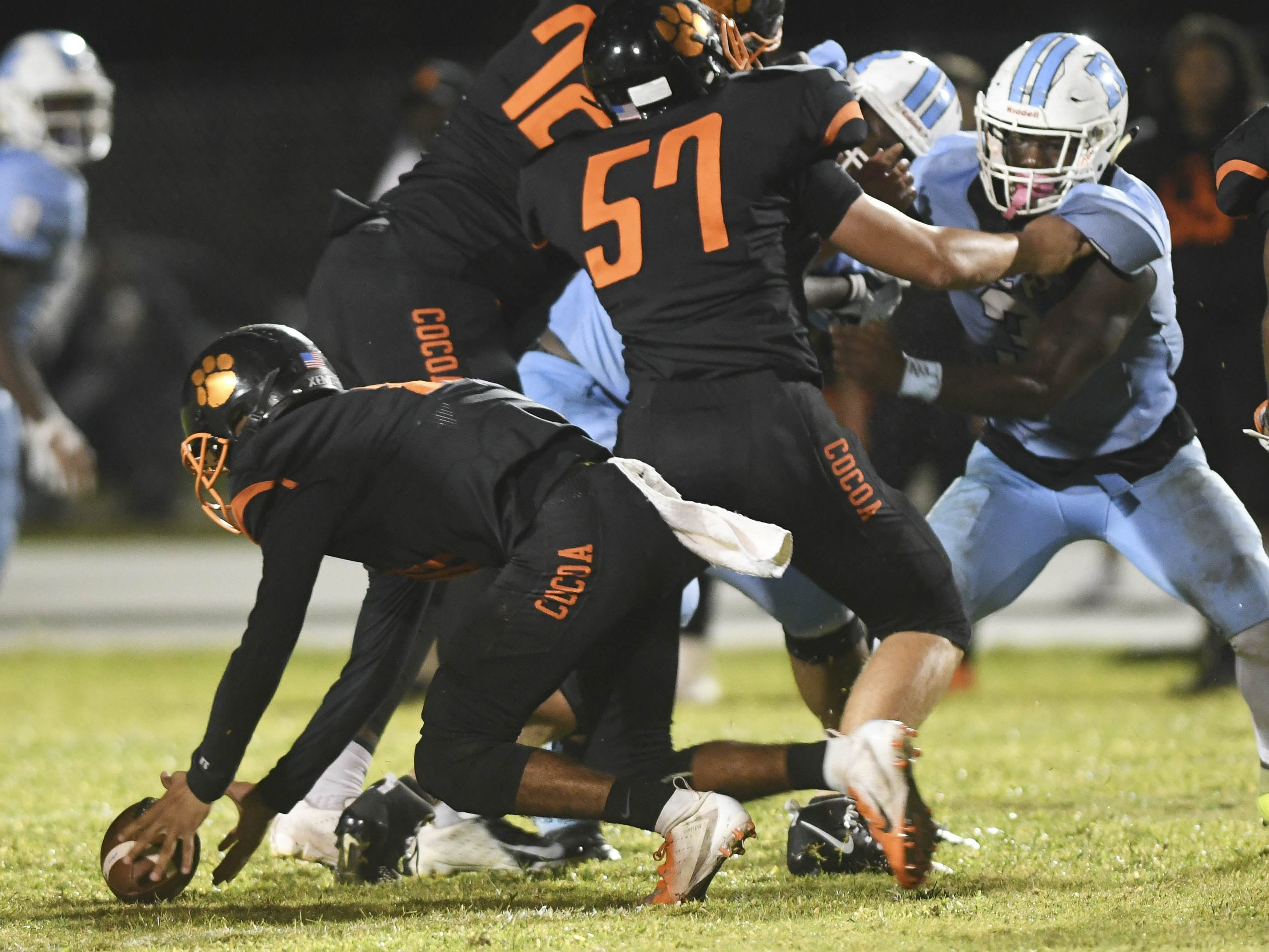 Cocoa QB Diego Arroyo picks up a fumble during Friday's game.