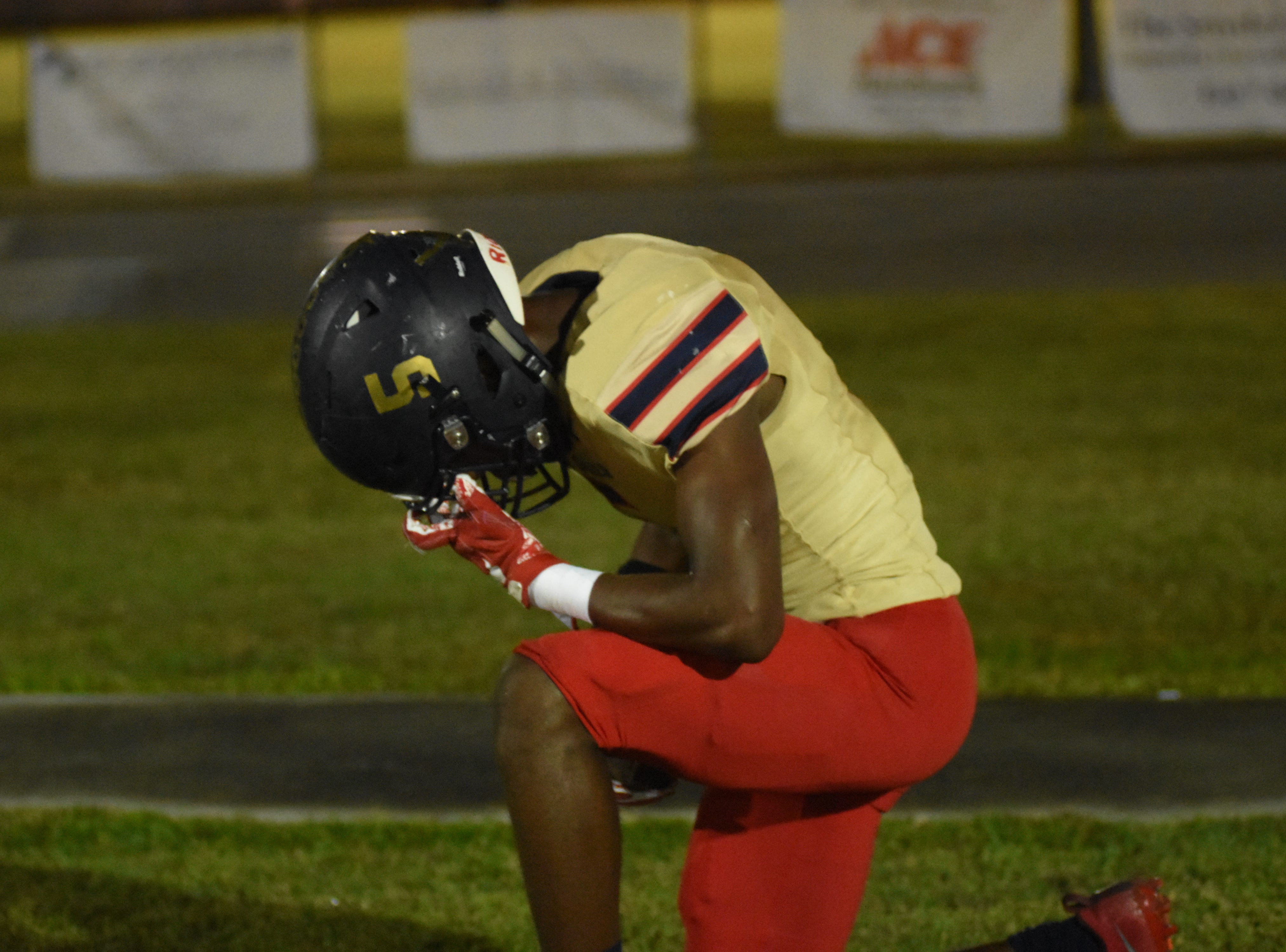 Eau Gallie's Jarrad Baker (5) takes a knee for a quick prayer after getting a touchdown to end the first quarter.