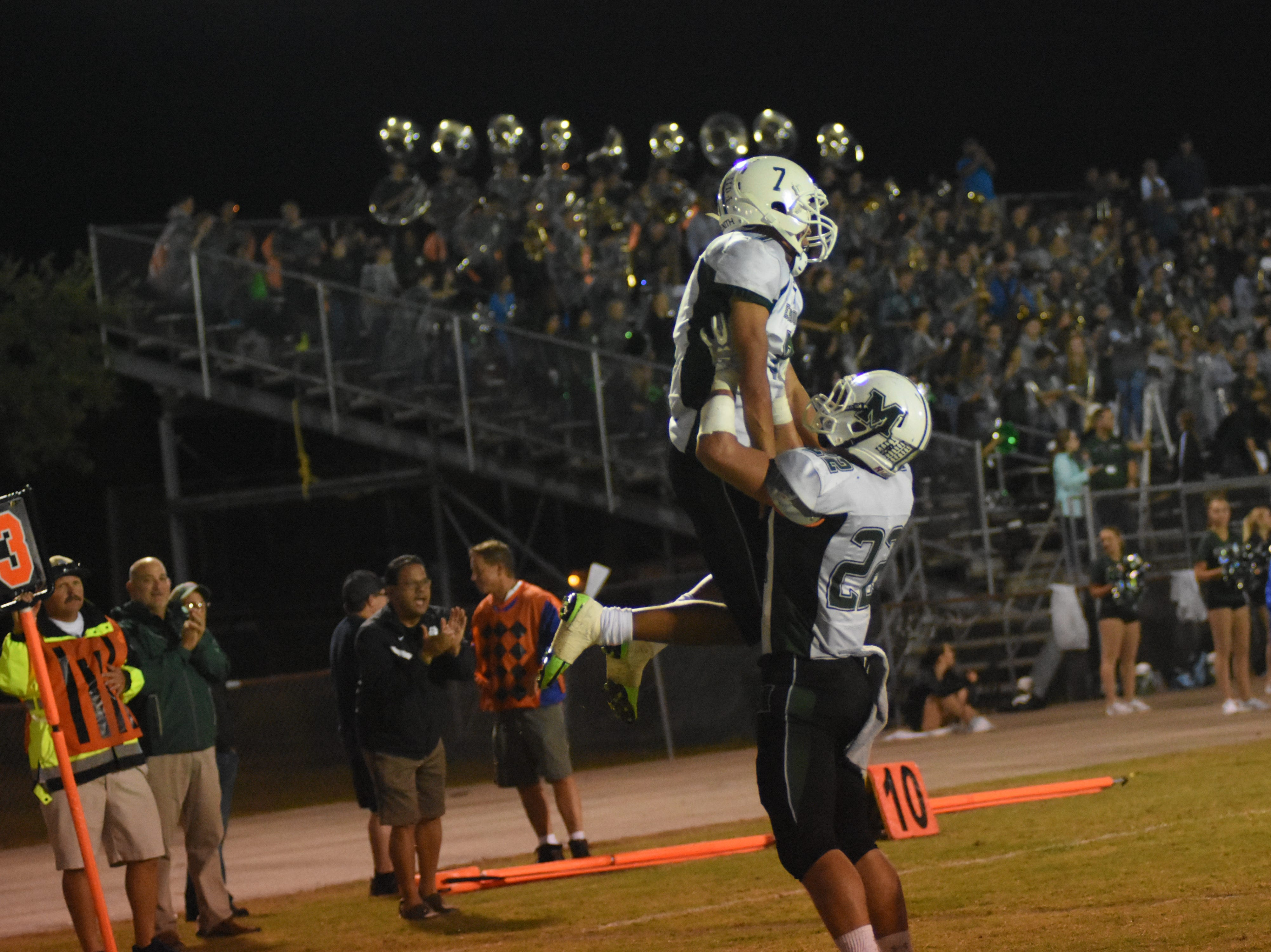 Melbourne High Bulldog Dalton Roseman (22) hoists Antionio Wright Jr. (7) into the air to celebrate Wright's touchdown.