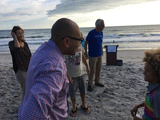 Sanjay Patel chats with 11-year-old climate activist Levi Draheim during a campaign event for Patel Saturday in Satellite Beach.