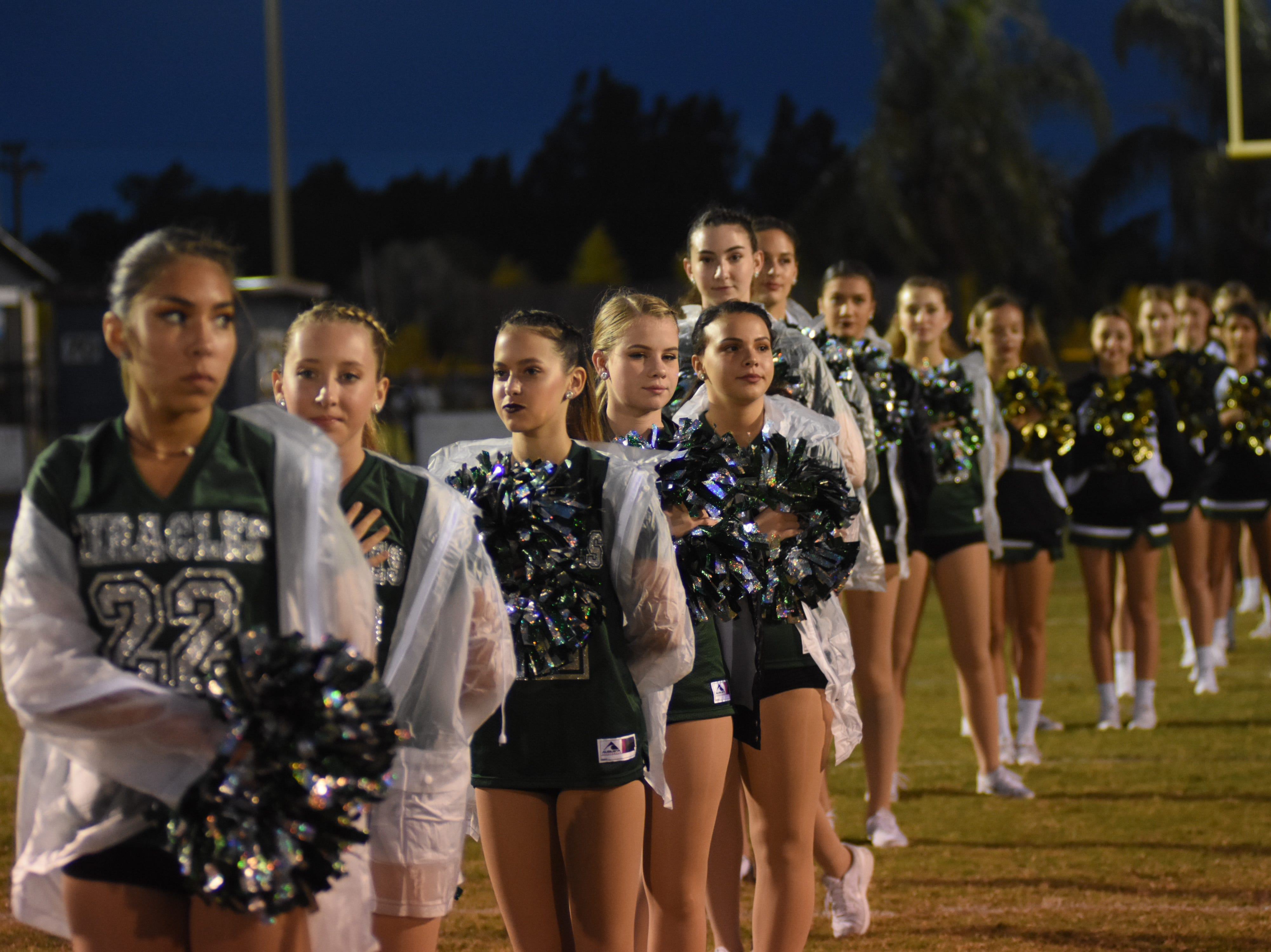 Melbourne High cheerleaders and Miracles stand during the National Anthem.