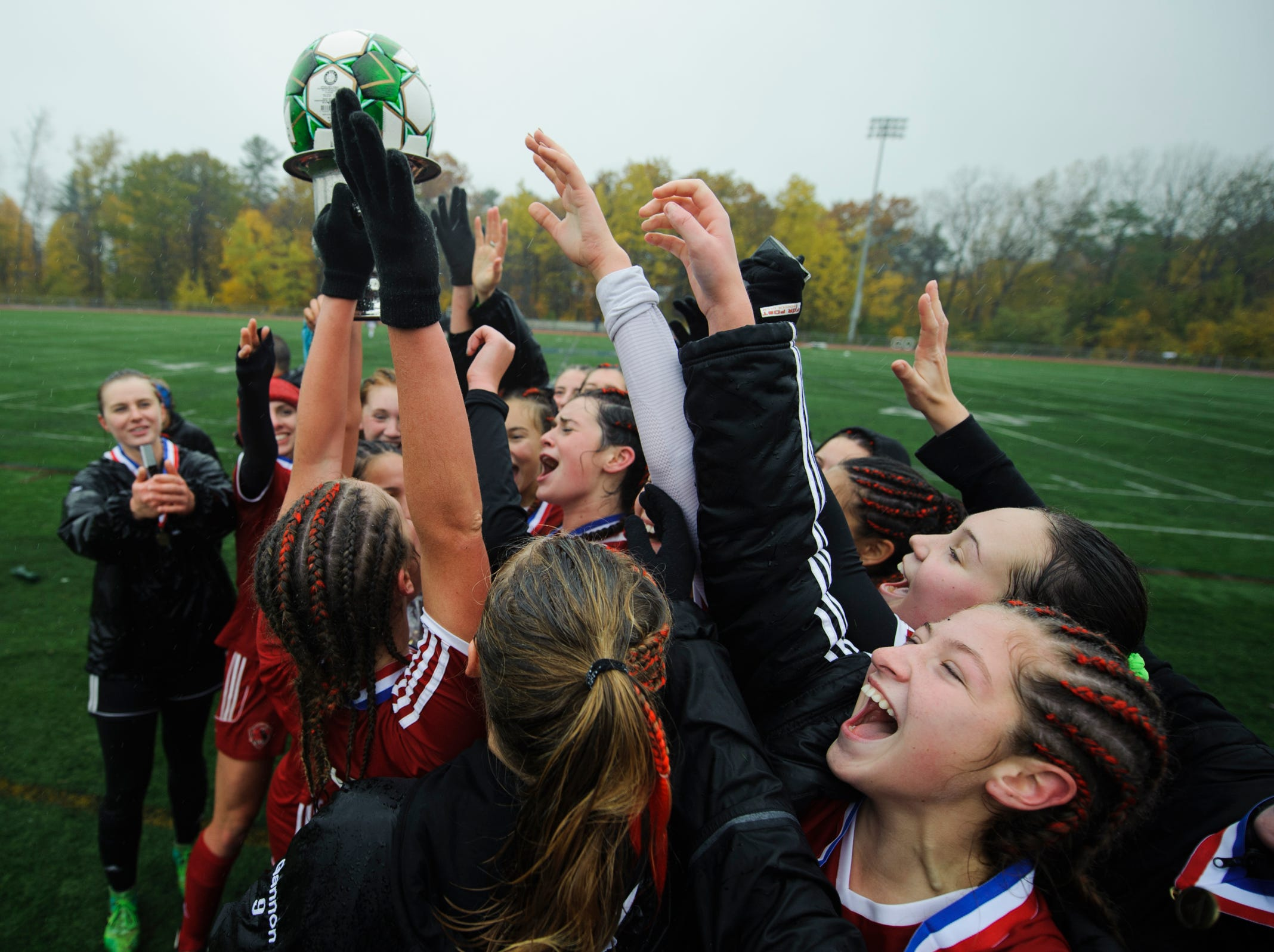 Champlain Valley players lit the trophy following their 1-0 win in the Division I girls soccer championship game between the Colchester Lakers and the Champlain Valley Union Redhawks at Buck Hard Field on Saturday morning November 3, 2018 in Burlington.